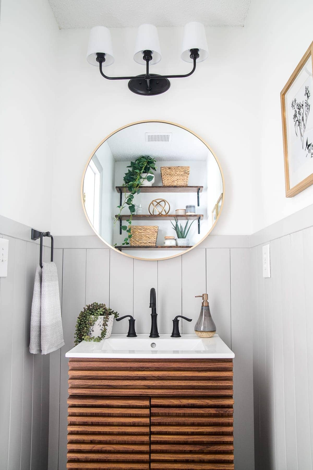 small bathroom with MCM sink vanity round mirror and shaded sconce