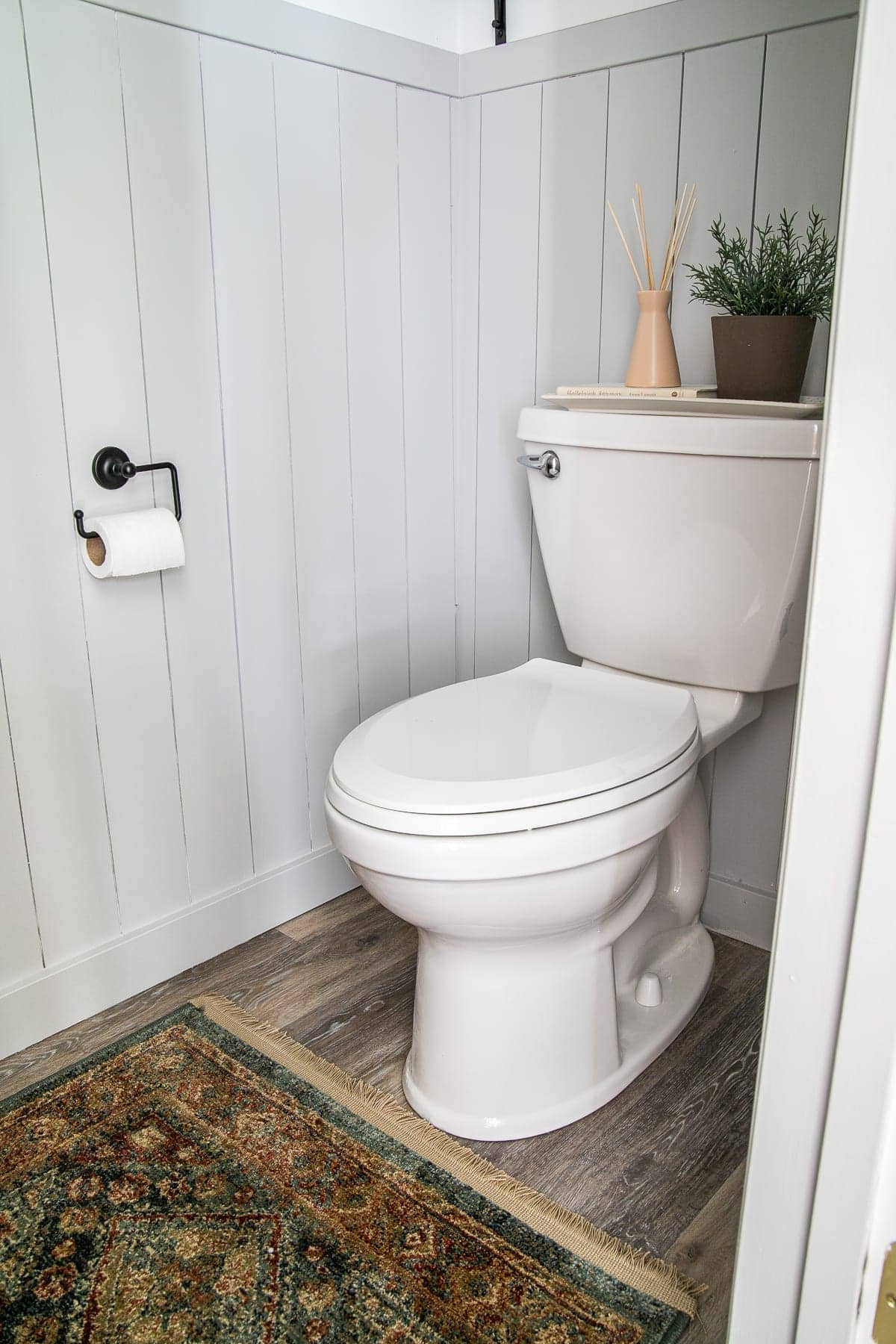 small bathroom with vertical shiplap and vintage style rug