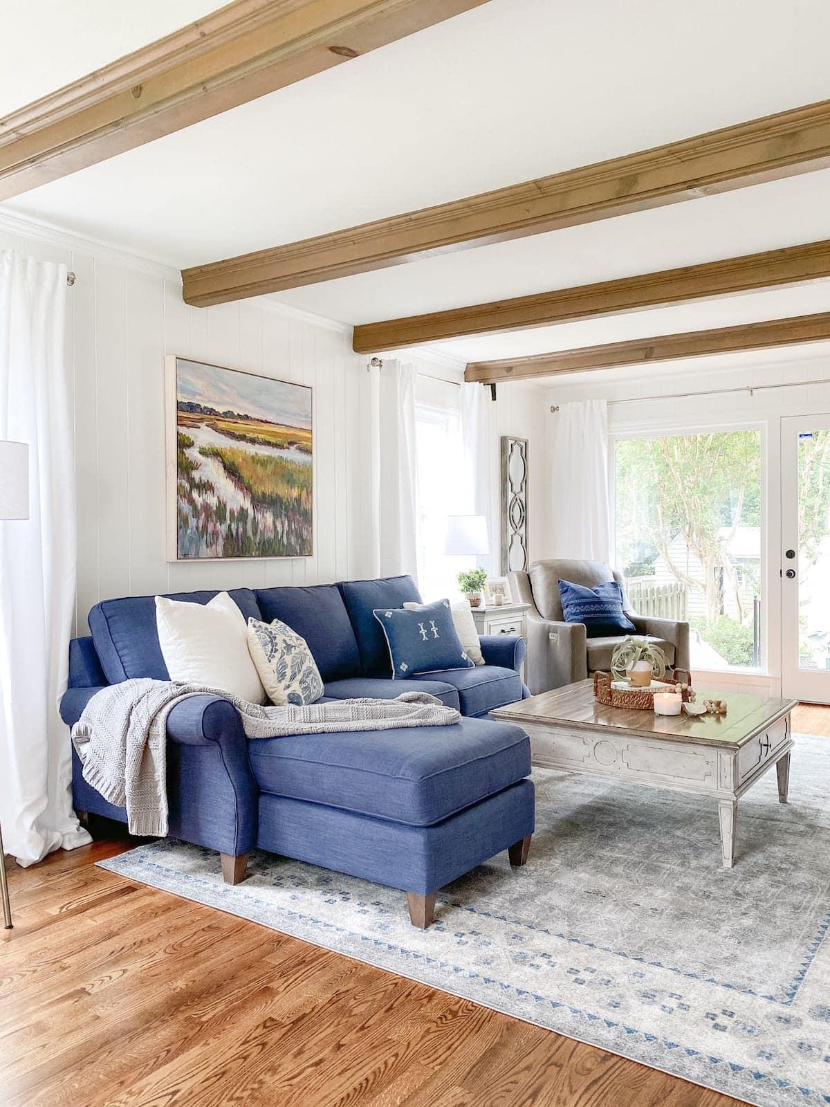 coastal living room with beams, navy sofa, rug, and weathered table