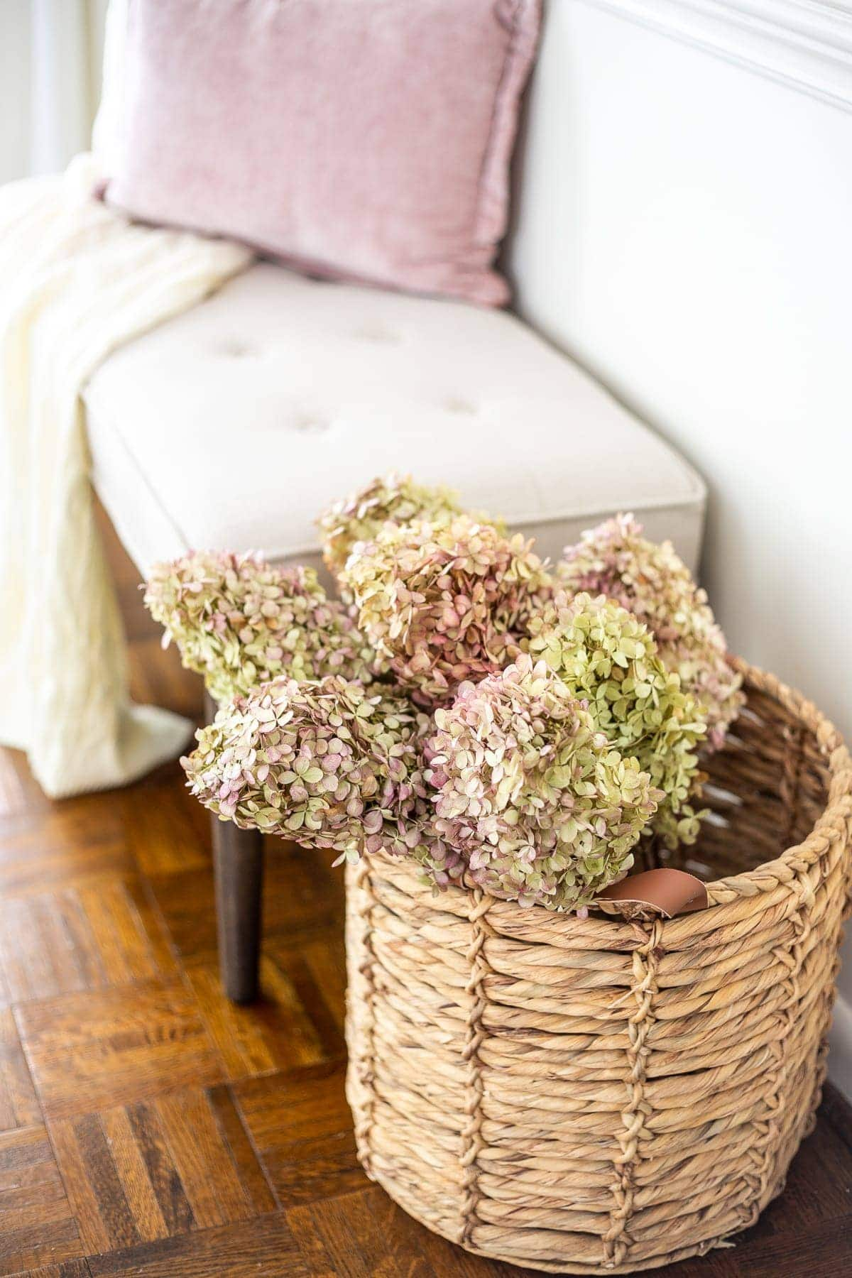 dried hydrangeas in a basket next to an entryway bench