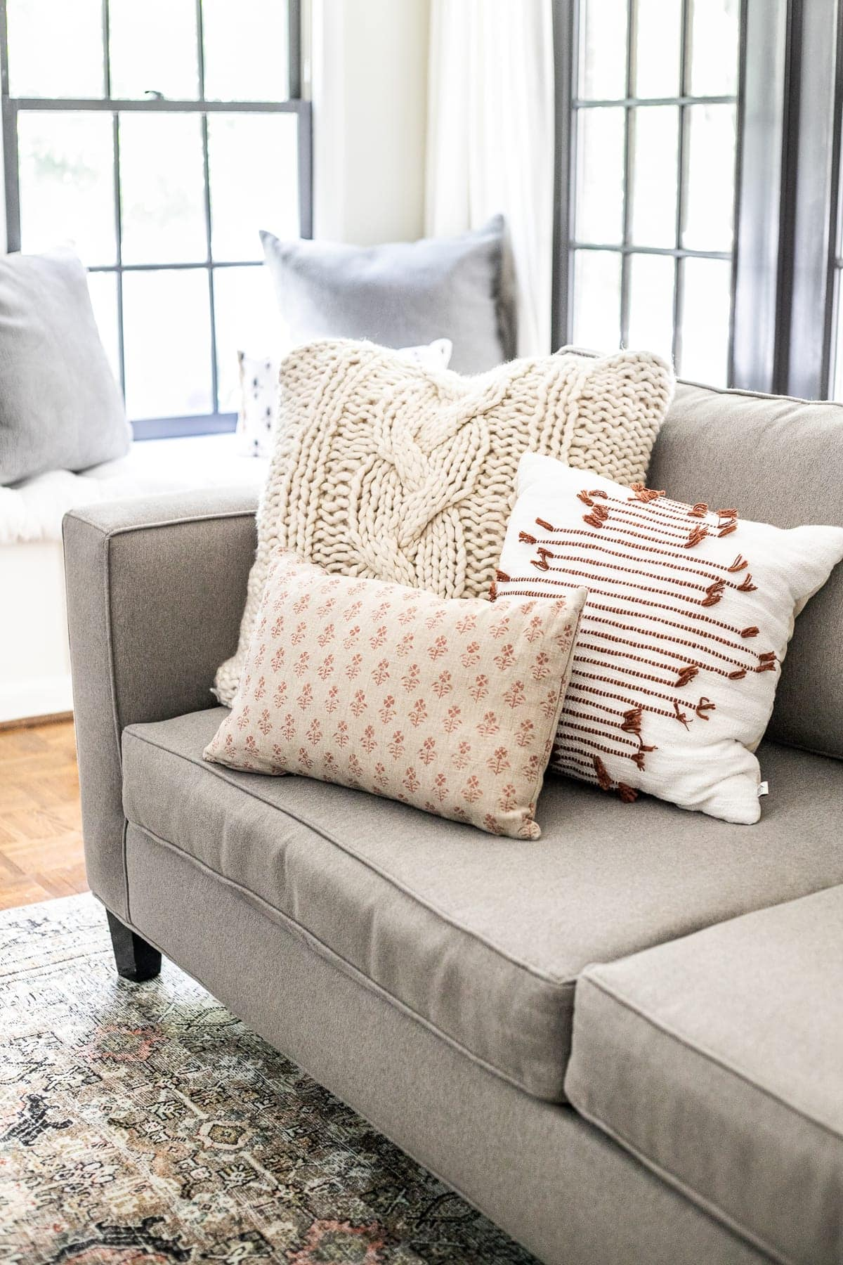 cable knit and rust colored fall throw pillows on sofa