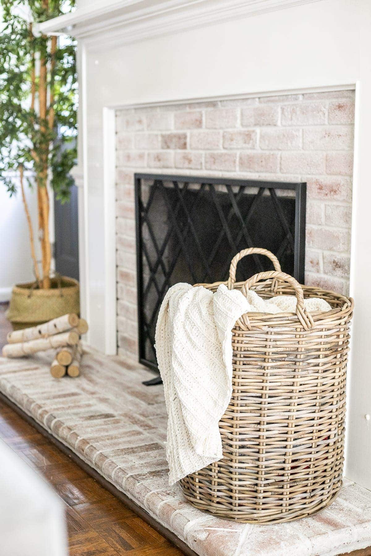 woven basket with cable knit throw blanket on limewashed brick fireplace