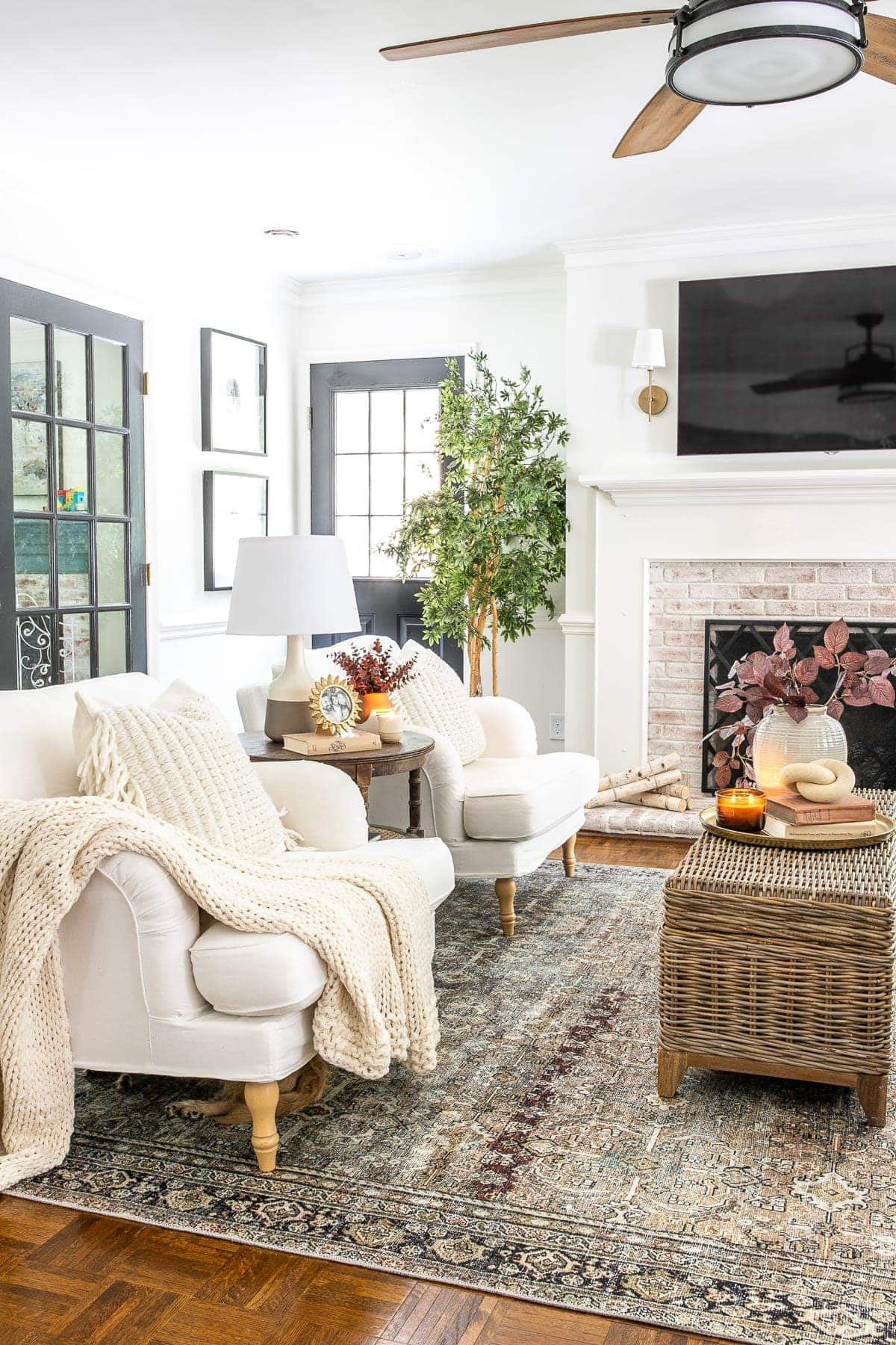 living room decorated for fall with rust and olive vintage style rug ceiling fan and TV above fireplace