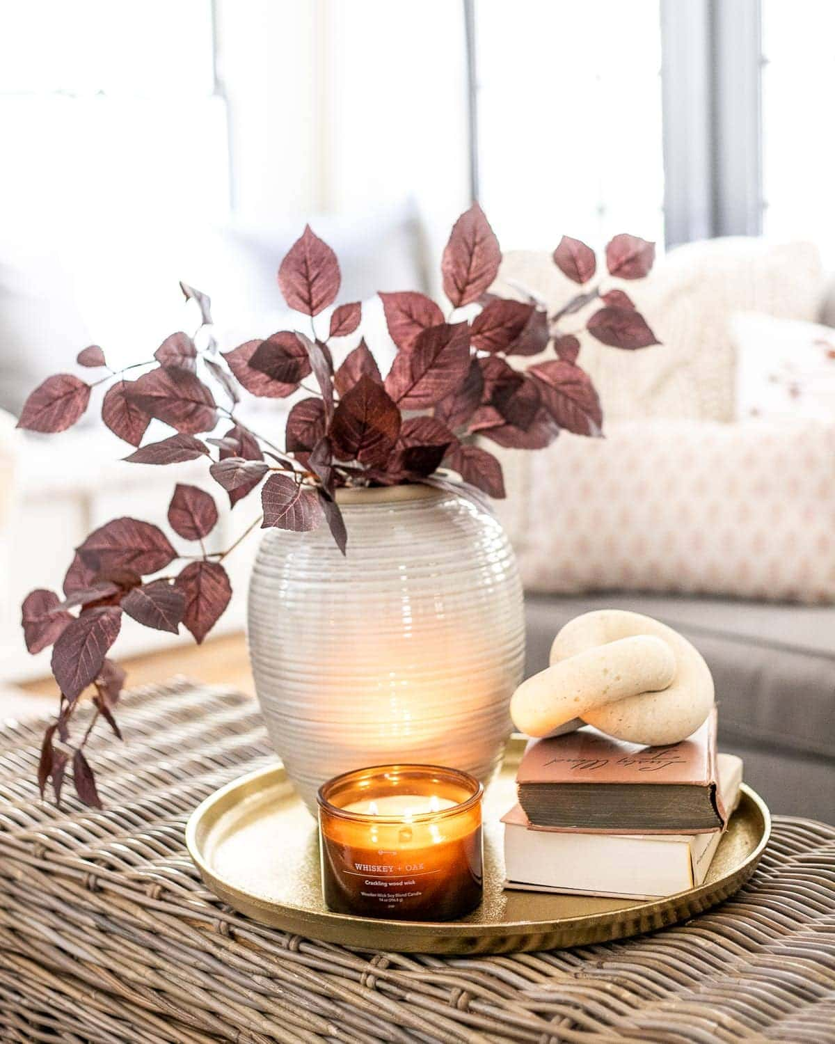 fall decor on a coffee table with brass tray, amber glass candle, wood knot, books, and vase with autumn stems