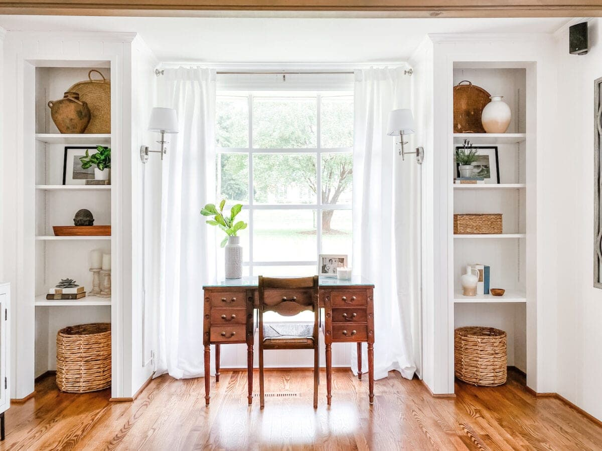 white office in living room with built-in shelves and desk in front of window