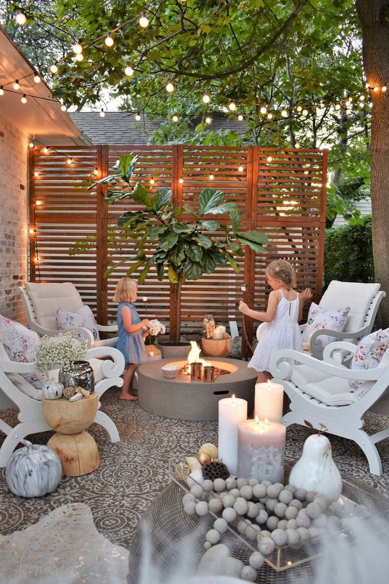 dreamy fire pit with string lights, wood screen, and limewashed brick