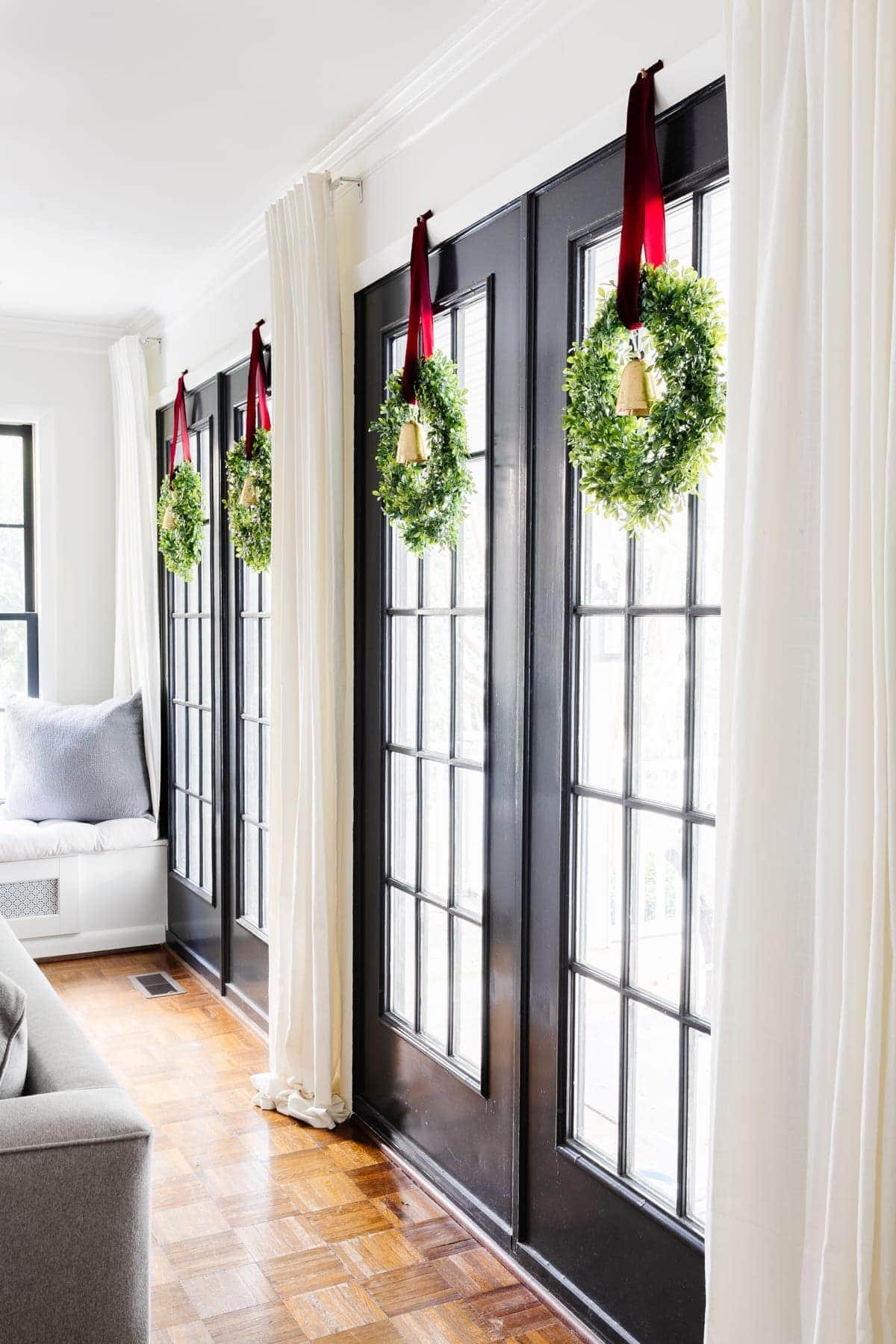 Christmas wreaths hanging on French door windows