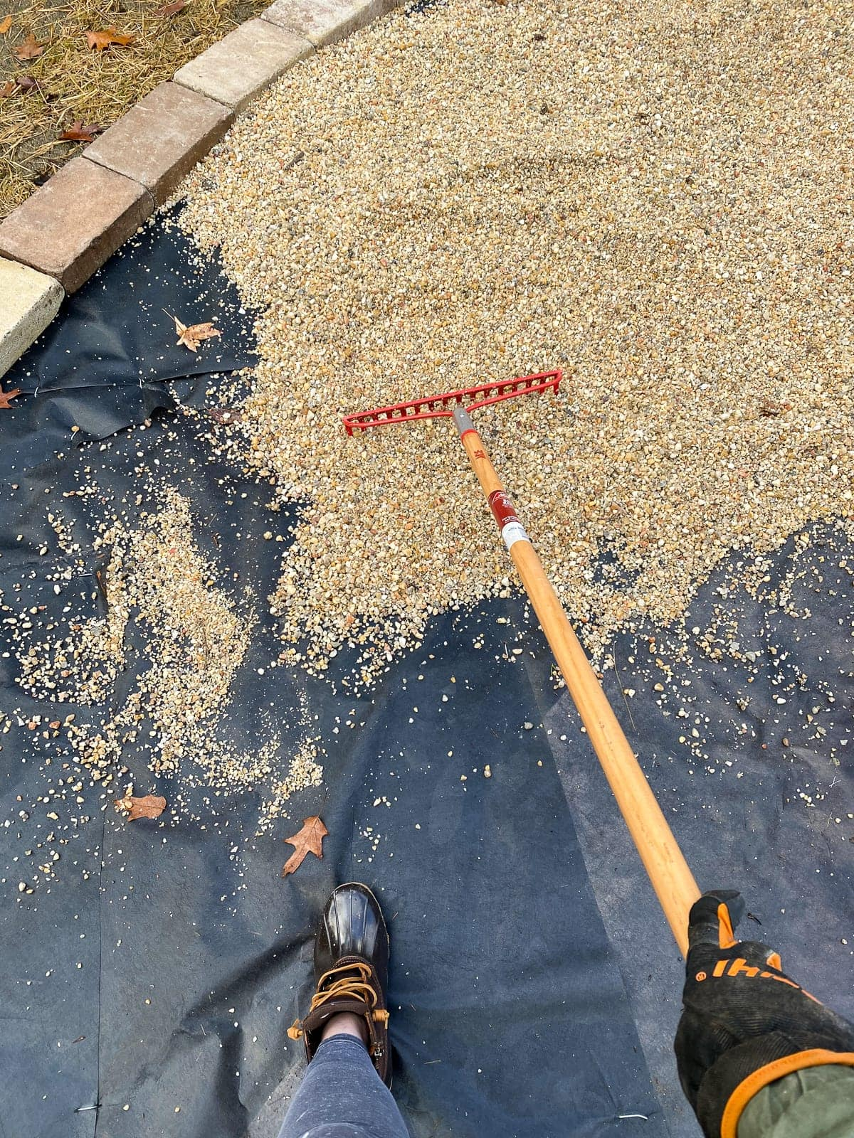Raking pea gravel on landscape fabric for a fire pit