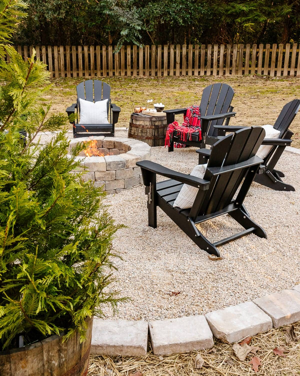 diy backyard fire pit with pea gravel, stone edgers, and adirondack chairs