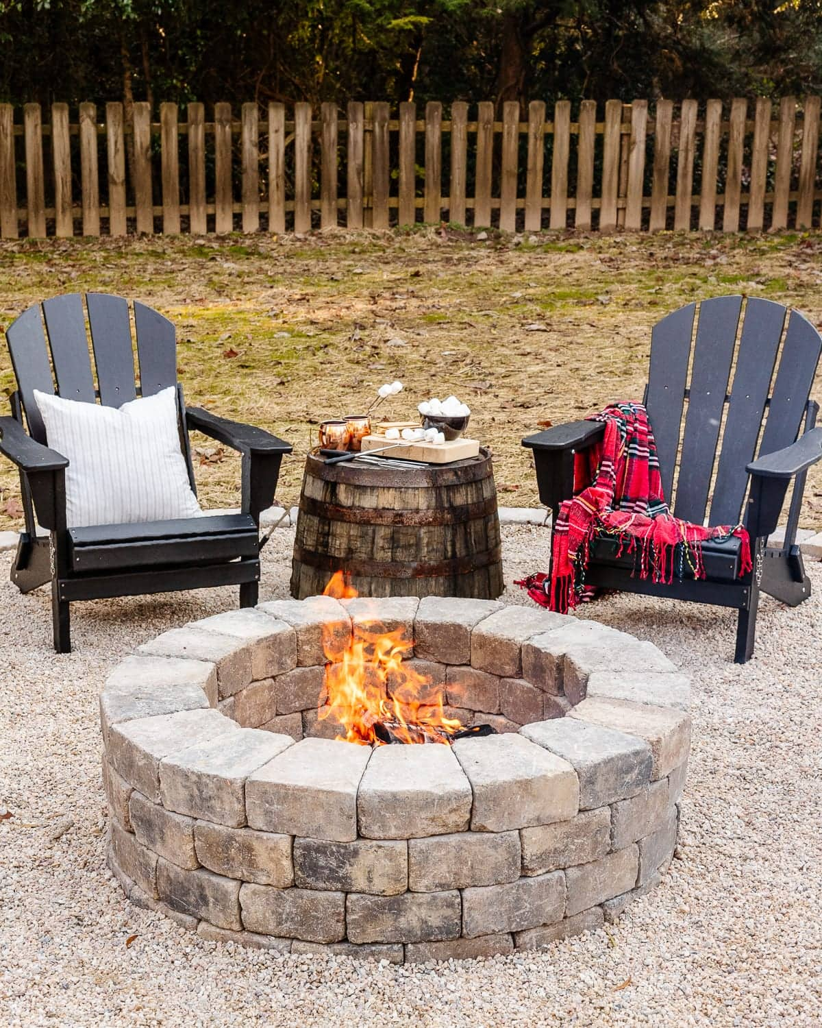 DIY fire pit with stone and pea gravel surrounded by adirondack chairs