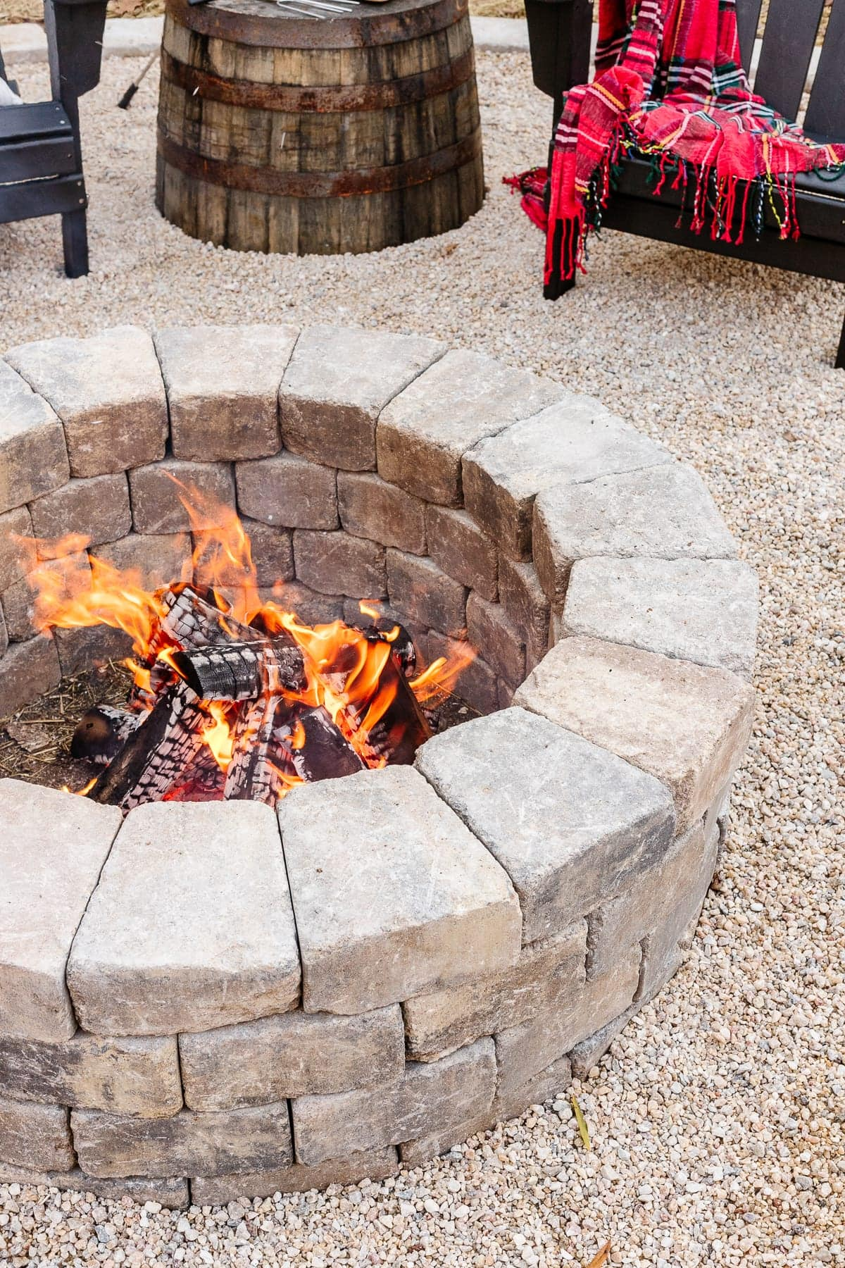 stone diy backyard fire pit with pea gravel and adirondack chairs