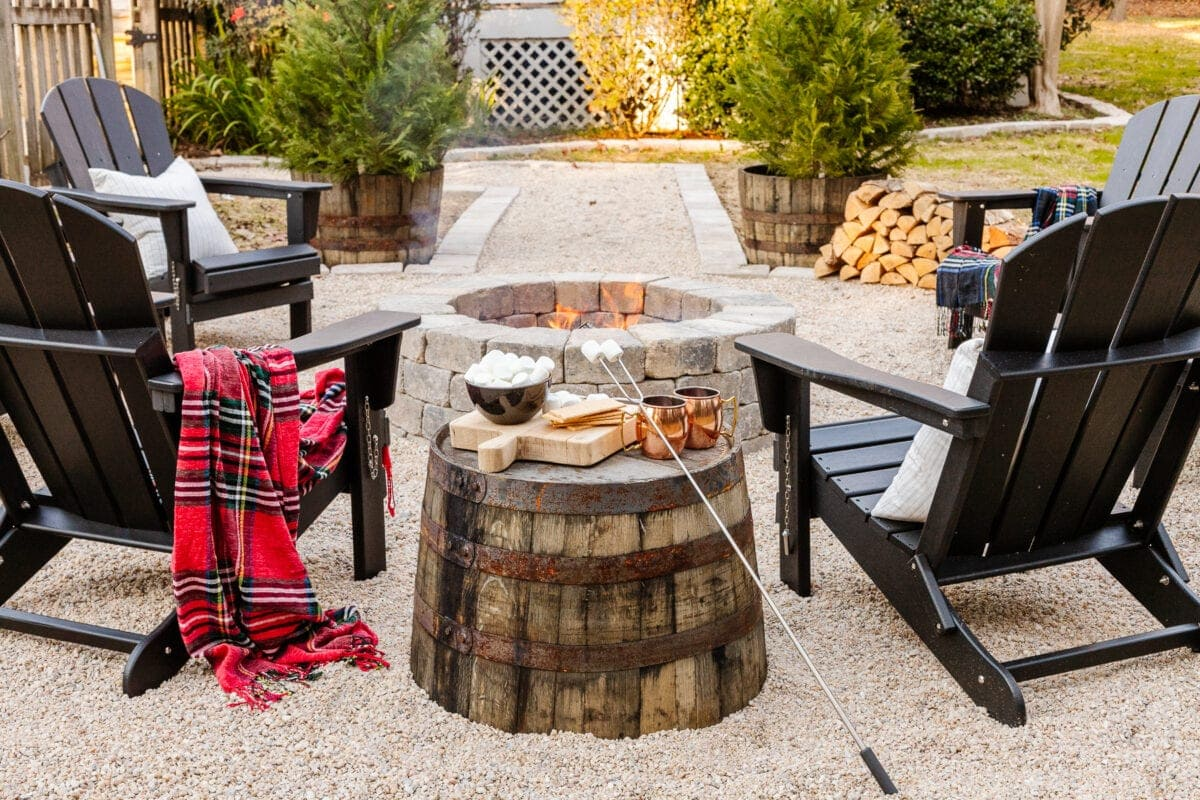 stone diy fire pit with pea gravel, stone edgers, and adirondack chairs with a barrel planter as a side table