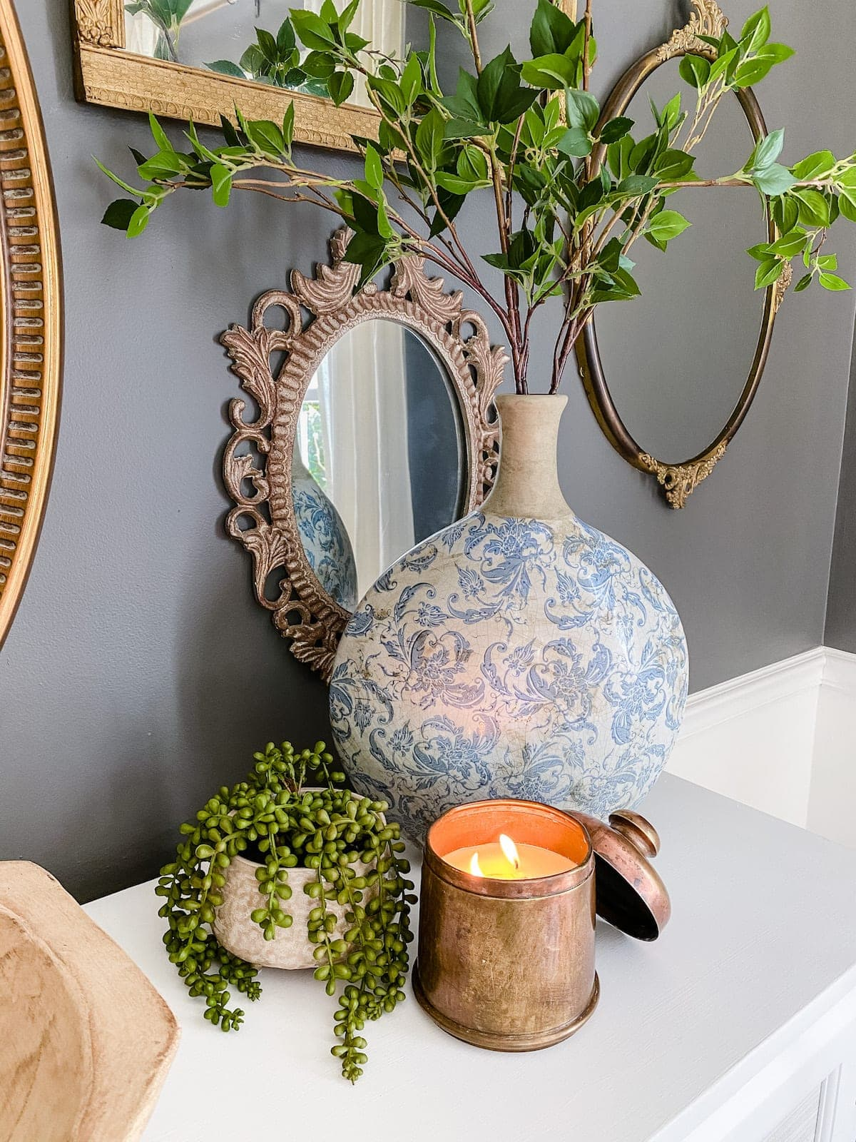antique brass canister candle with Chinoiserie vase and greenery