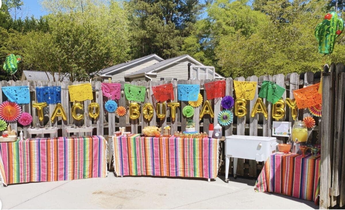 baby shower taco bar decorated with Mexican serape tablecloths and balloons