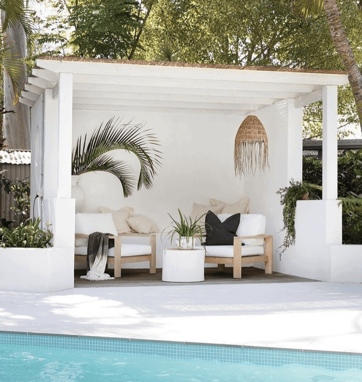 tropical plants and rattan pendant light in a white pool cabana