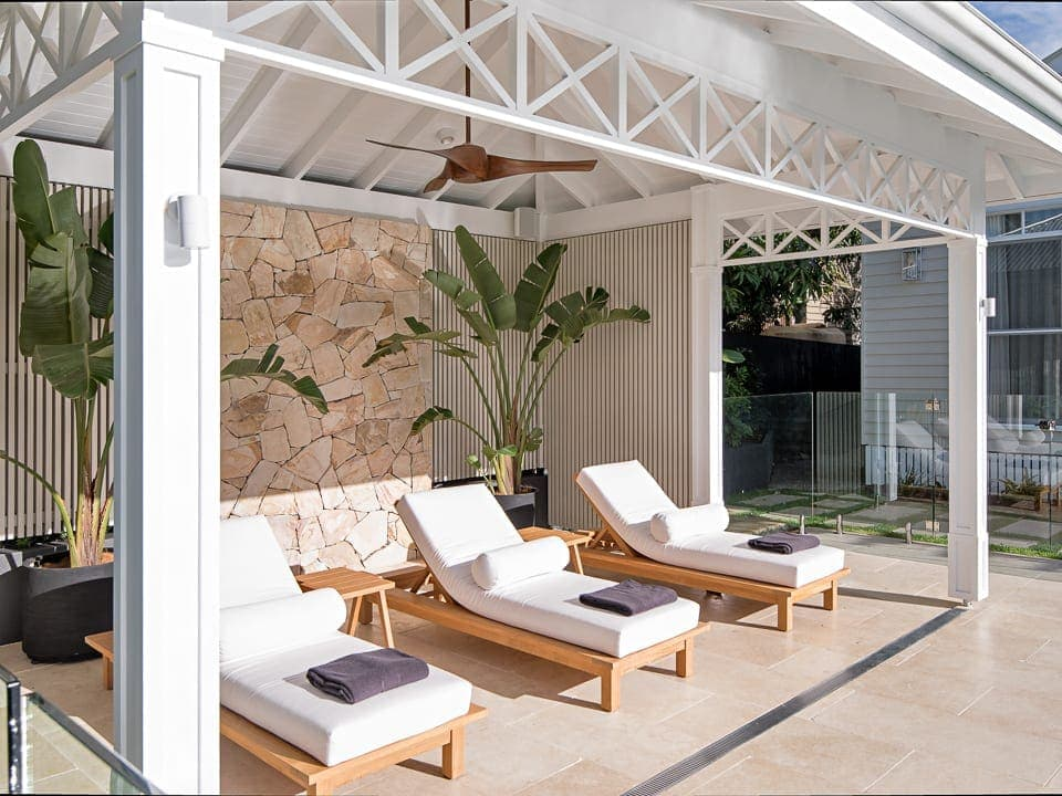 white cabana with outdoor lounge chairs and stone wall