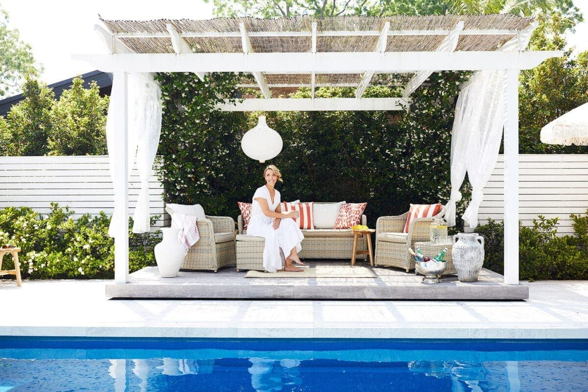 pool cabana with white gauze curtains and rattan outdoor furniture