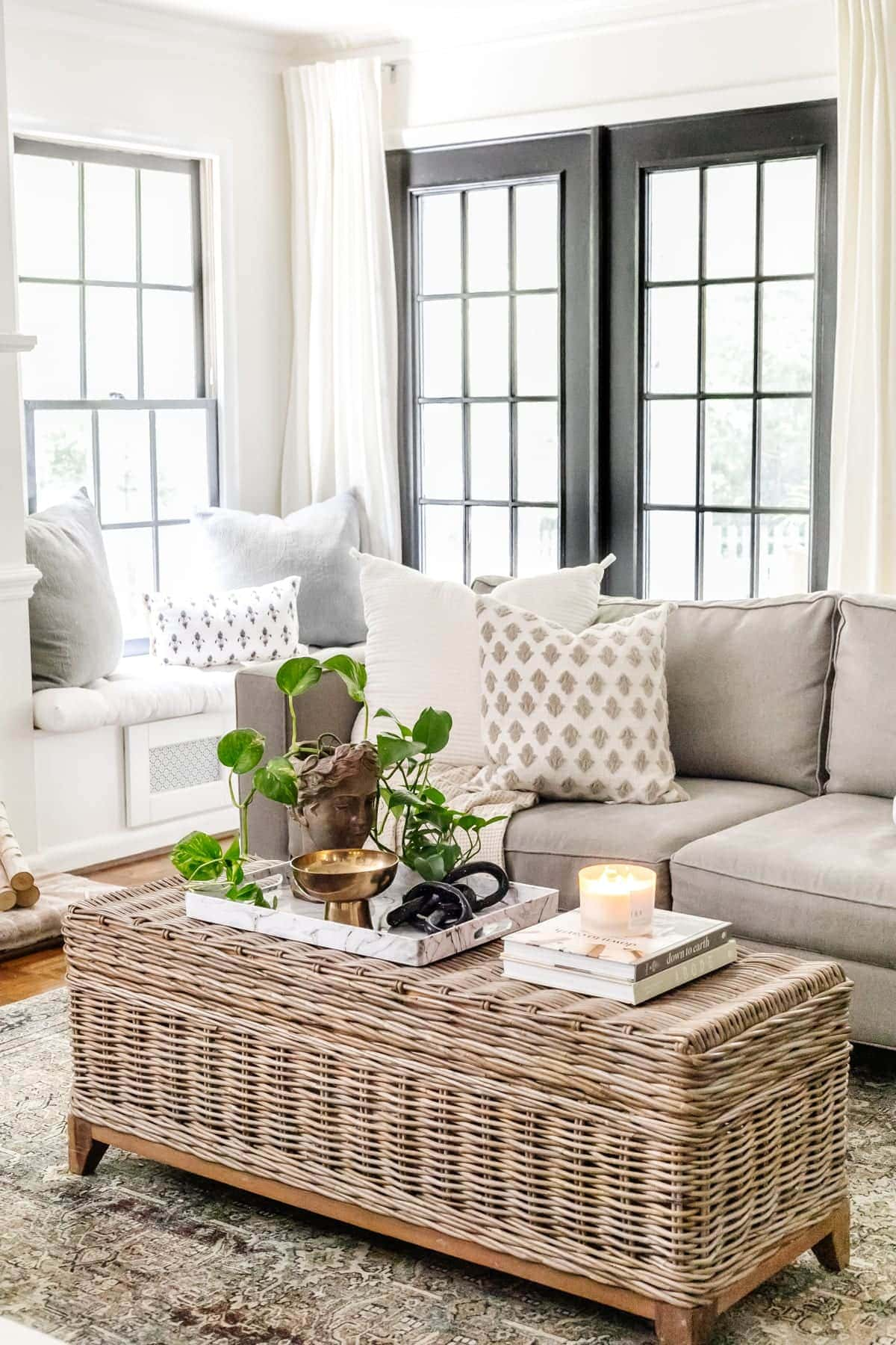 rattan coffee table in a living room with black doors