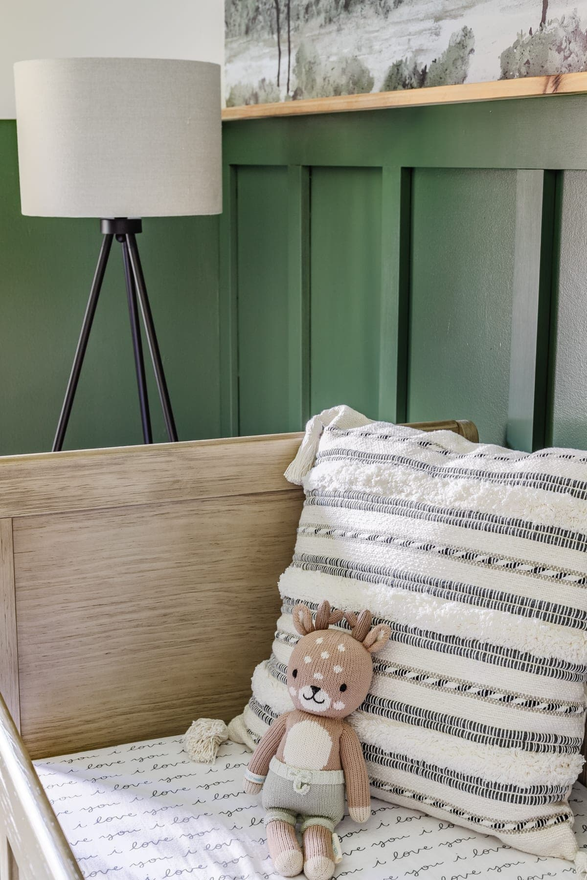 baby boy nursery with woodland theme - floor lamp and pillow with natural wood crib