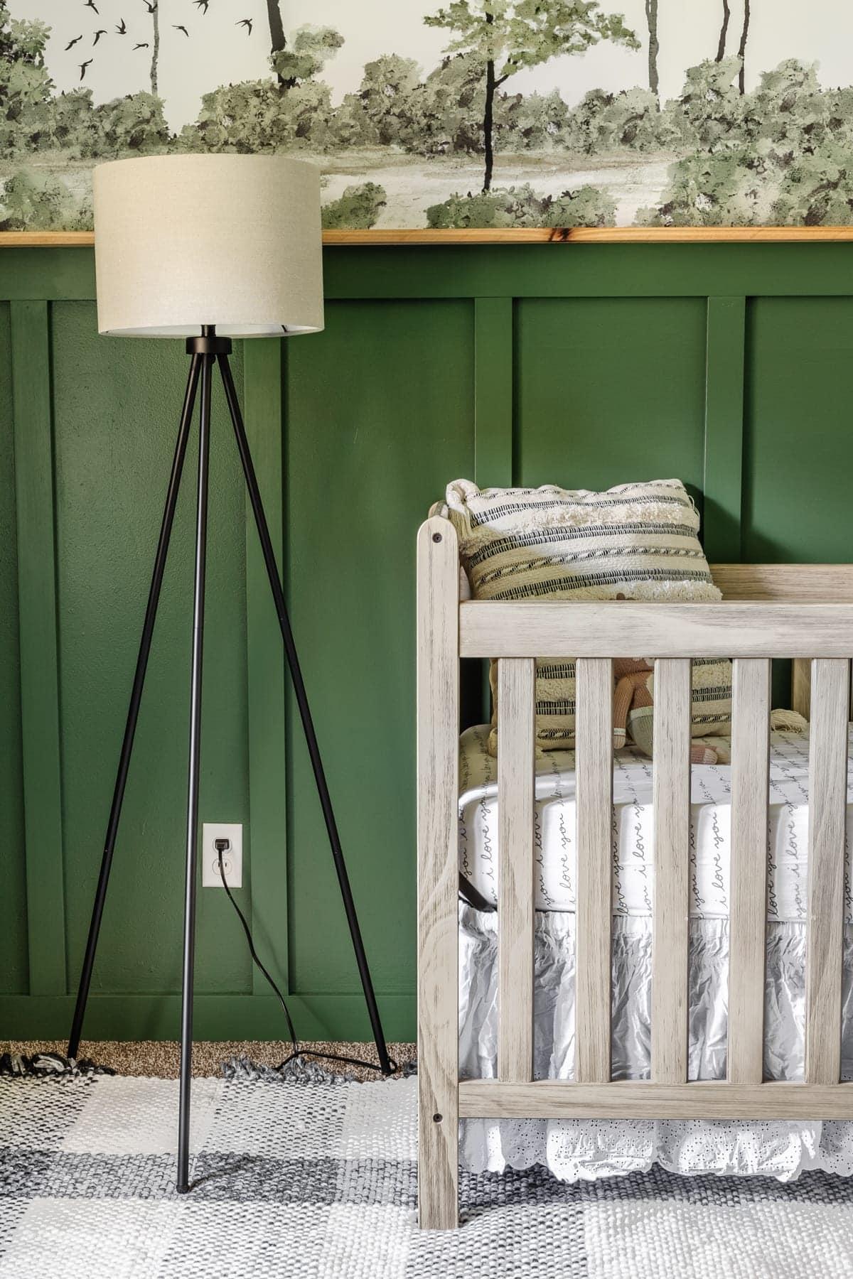 woodland theme baby boy nursery with floor lamp, natural wood crib, plaid rug, and wall mural