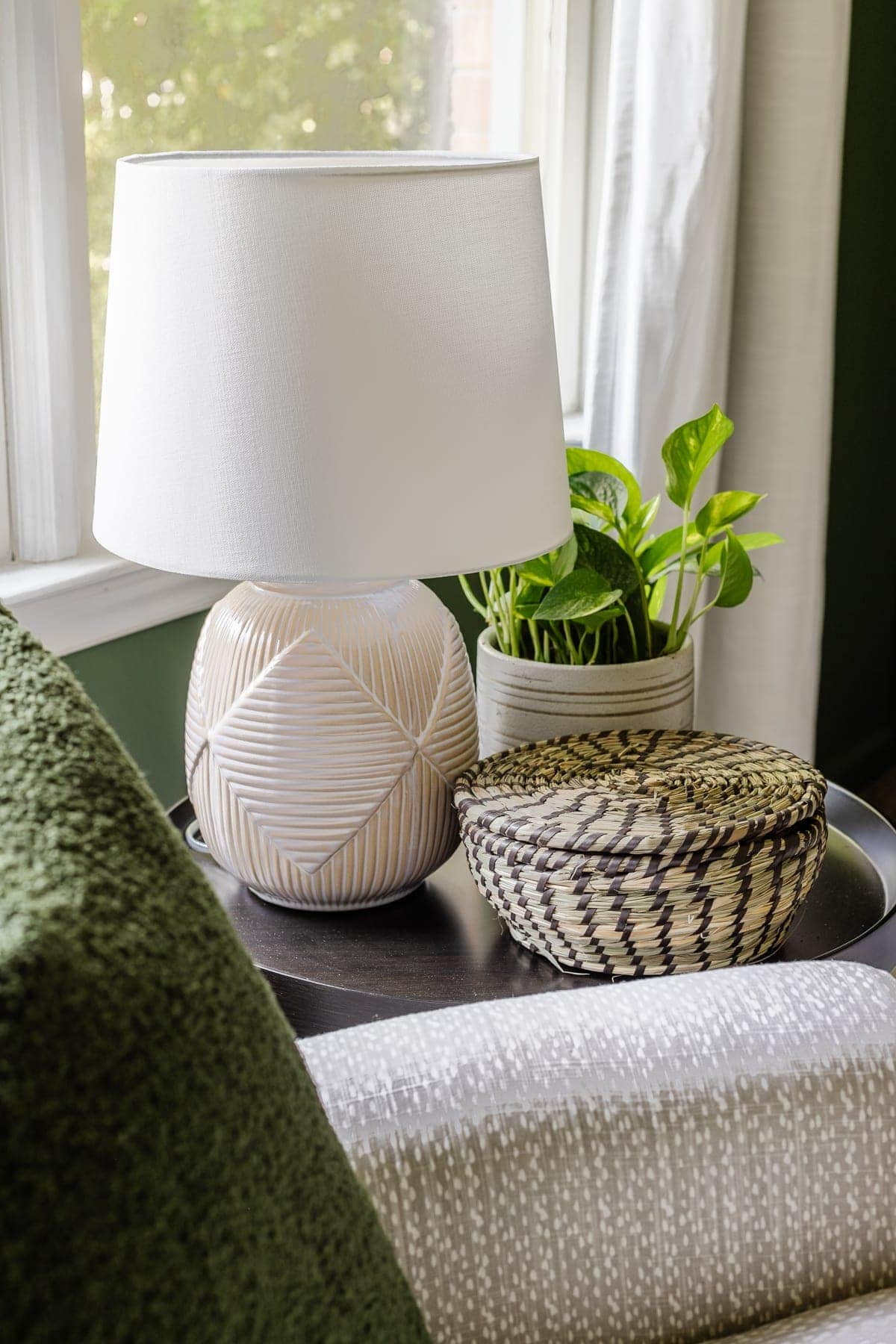 nursery side table with lamp, plant, and lidded basket for holding baby essentials