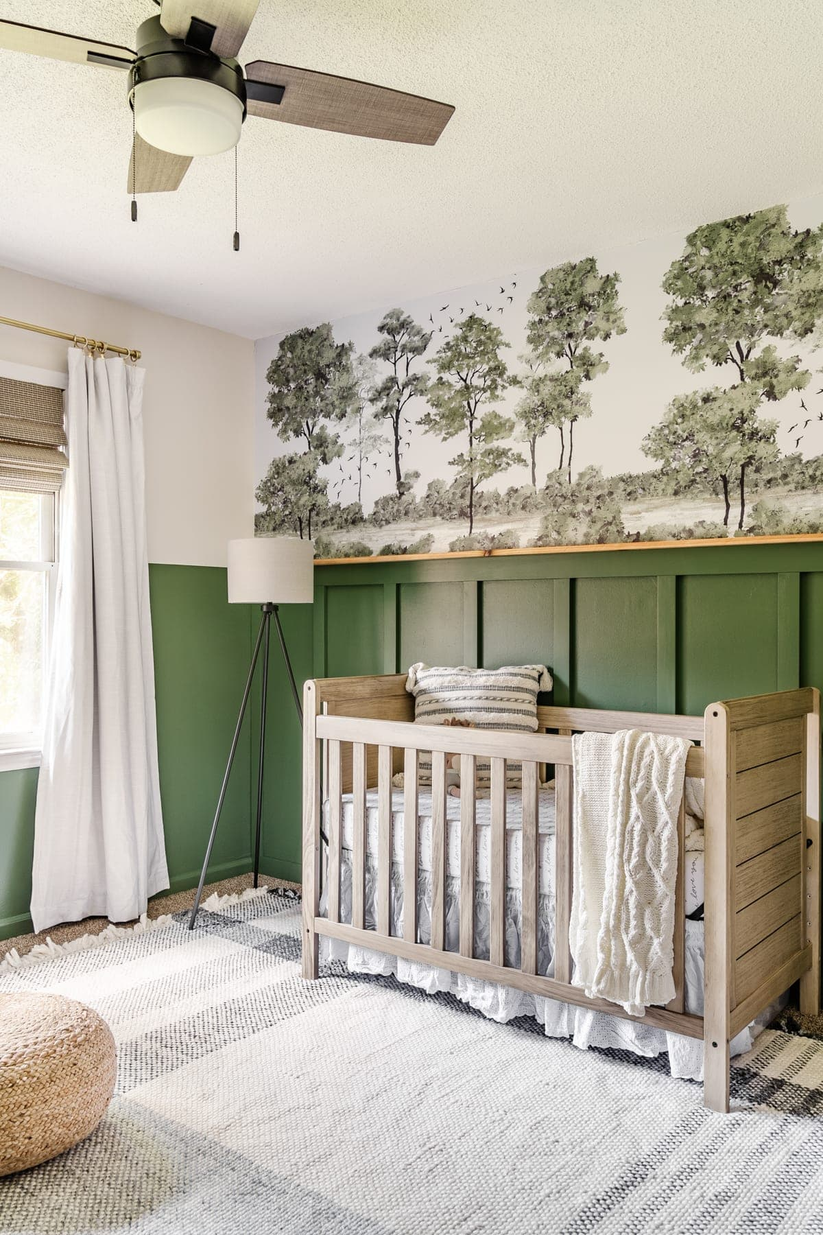 boy nursery with green paint and forest wall mural