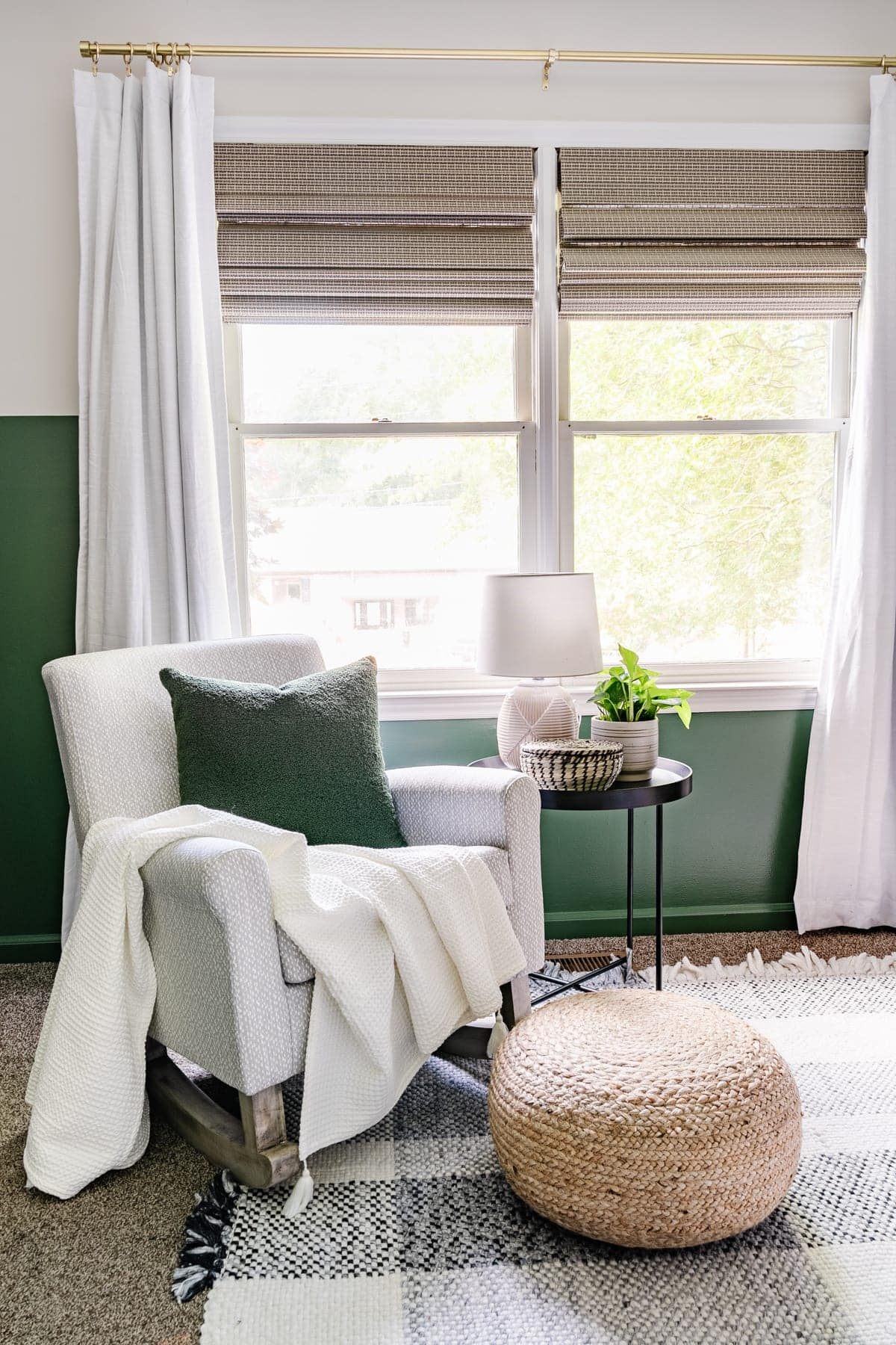 nursery with green paint, plaid rug, and gray rocking chair