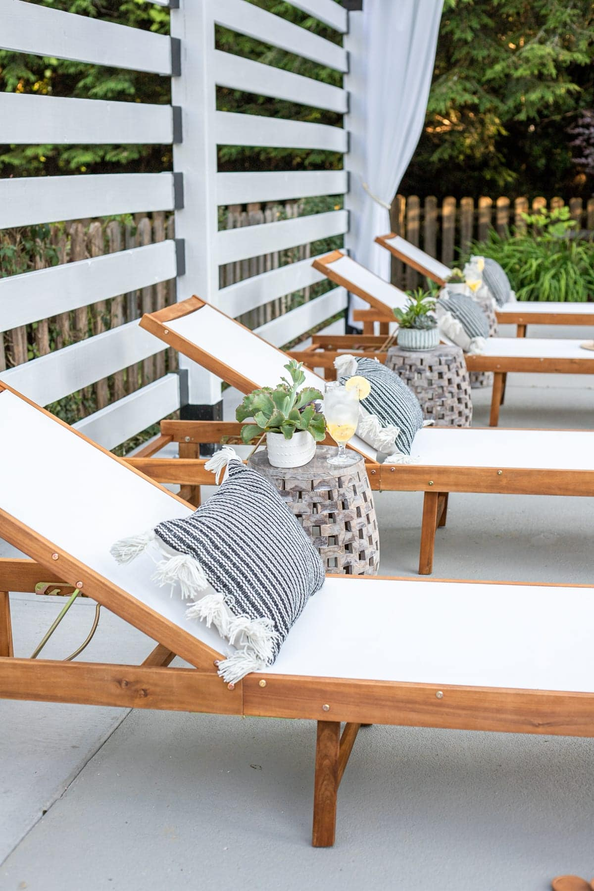 outdoor lounge chairs under white pergola with outdoor curtains and pillows