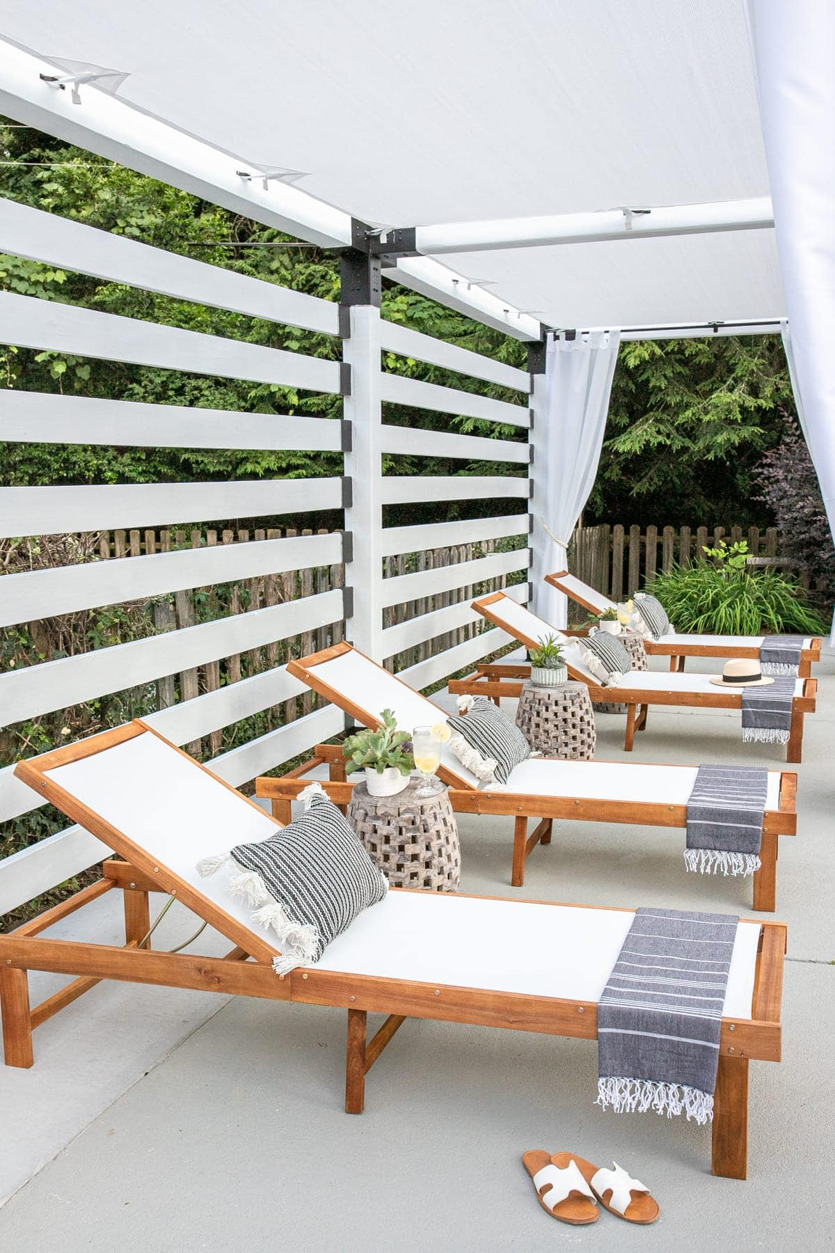 pool lounge chairs under a white DIY pergola