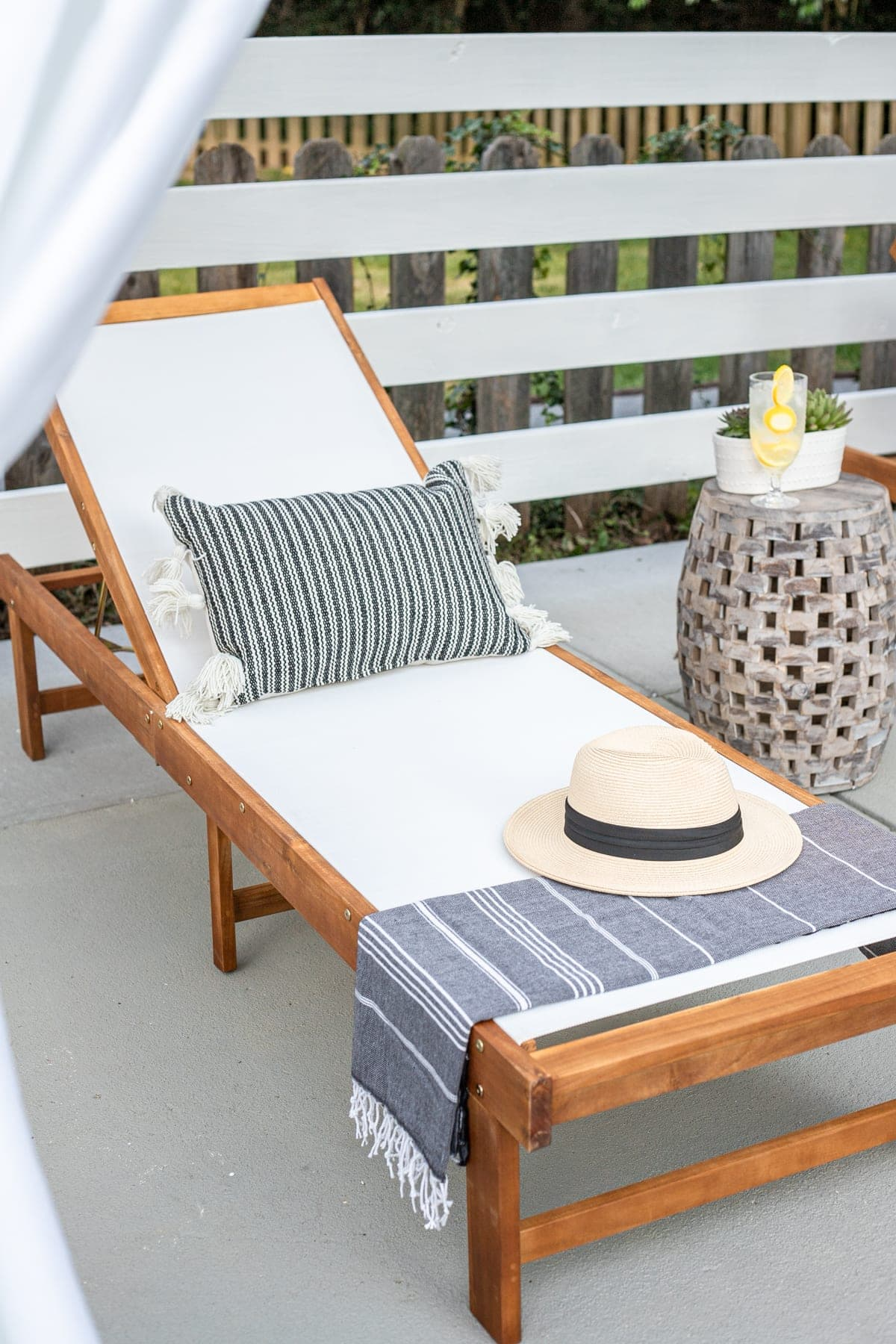 outdoor lounge chair with pillow, turkish towel, and sun hat