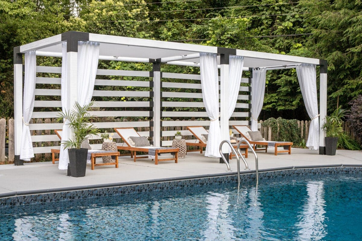white DIY pergola cabana with outdoor curtains and lounge chairs