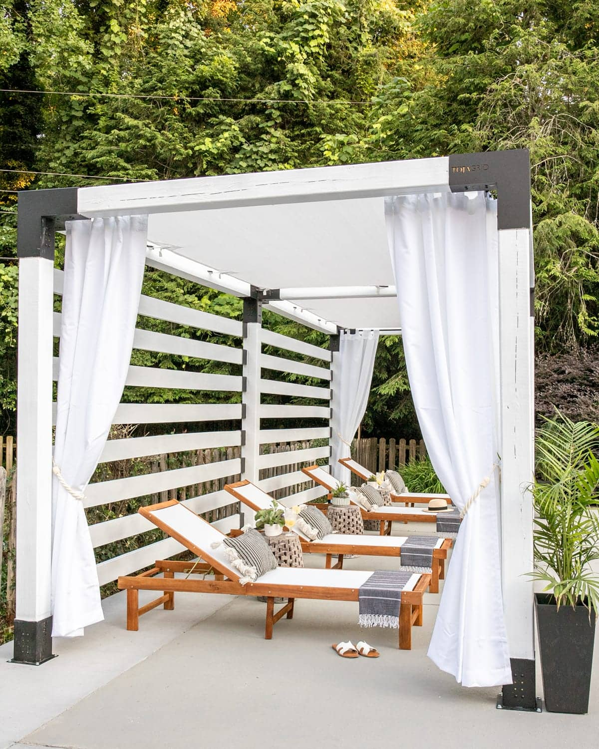 outdoor lounge chairs under a white pergola cabana with outdoor curtains