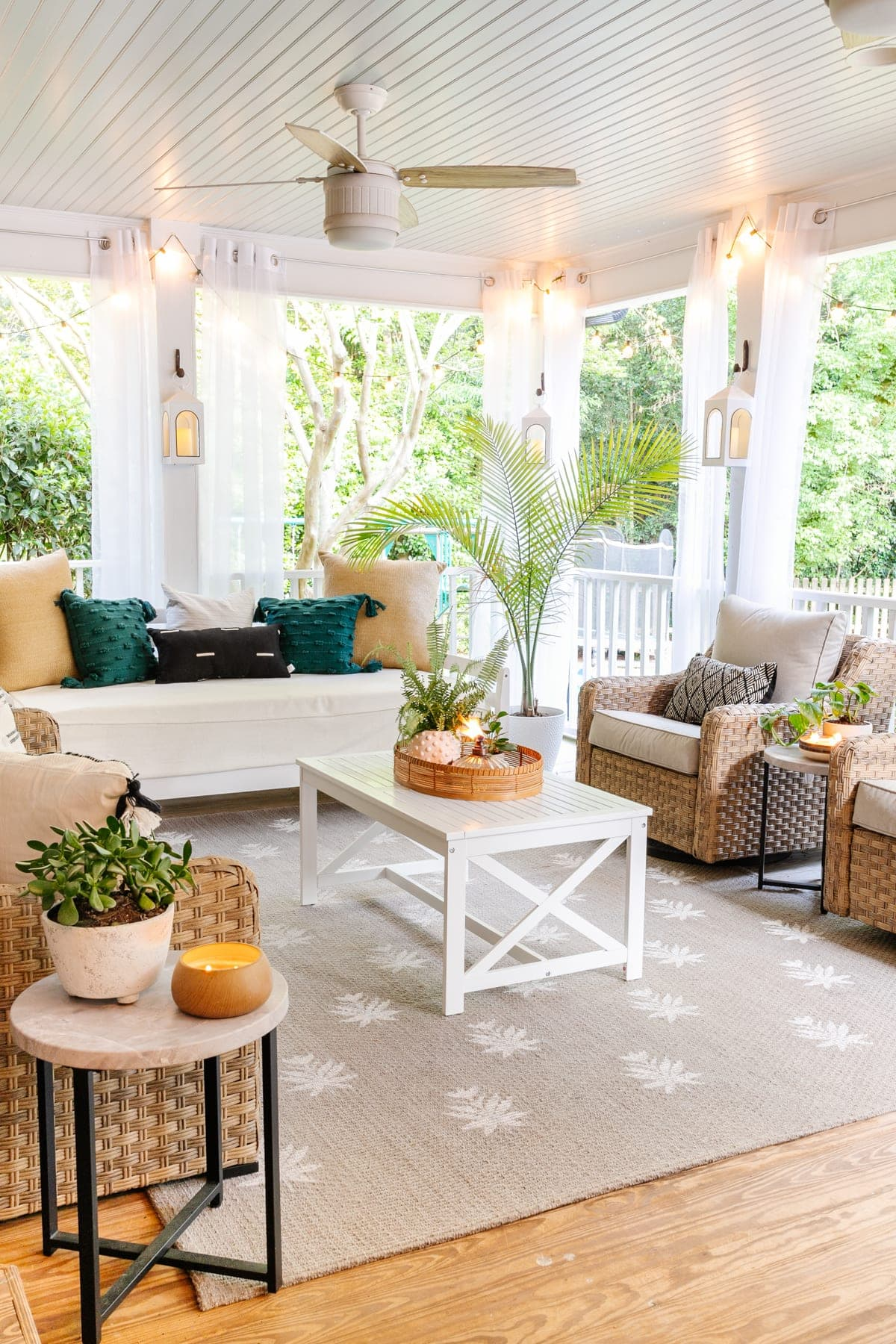 back porch with coffee table, conversation set, day bed, outdoor ceiling fans and DIY floral block rug made from a Cricut machine stencil