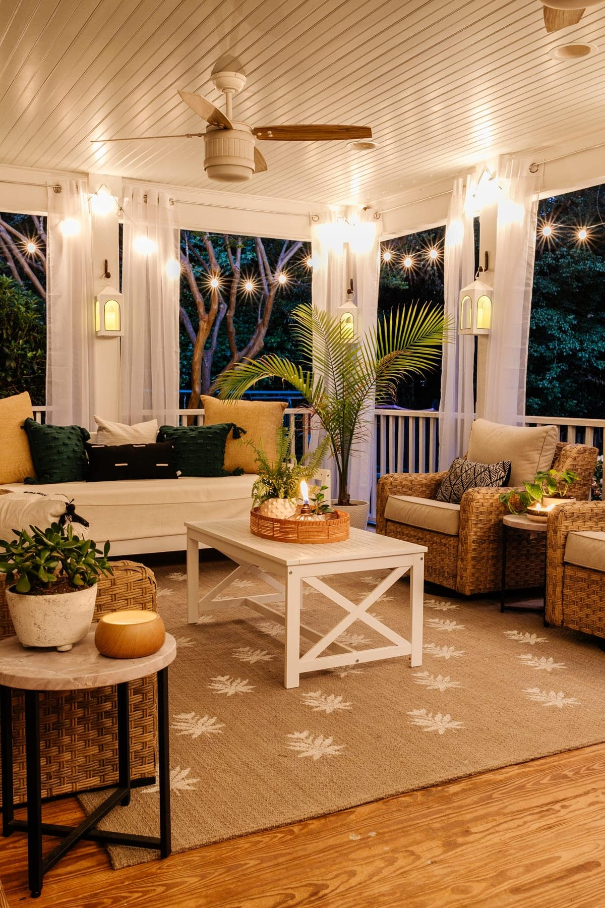 back porch at night with twinkle lights, candles, and floral block DIY outdoor rug