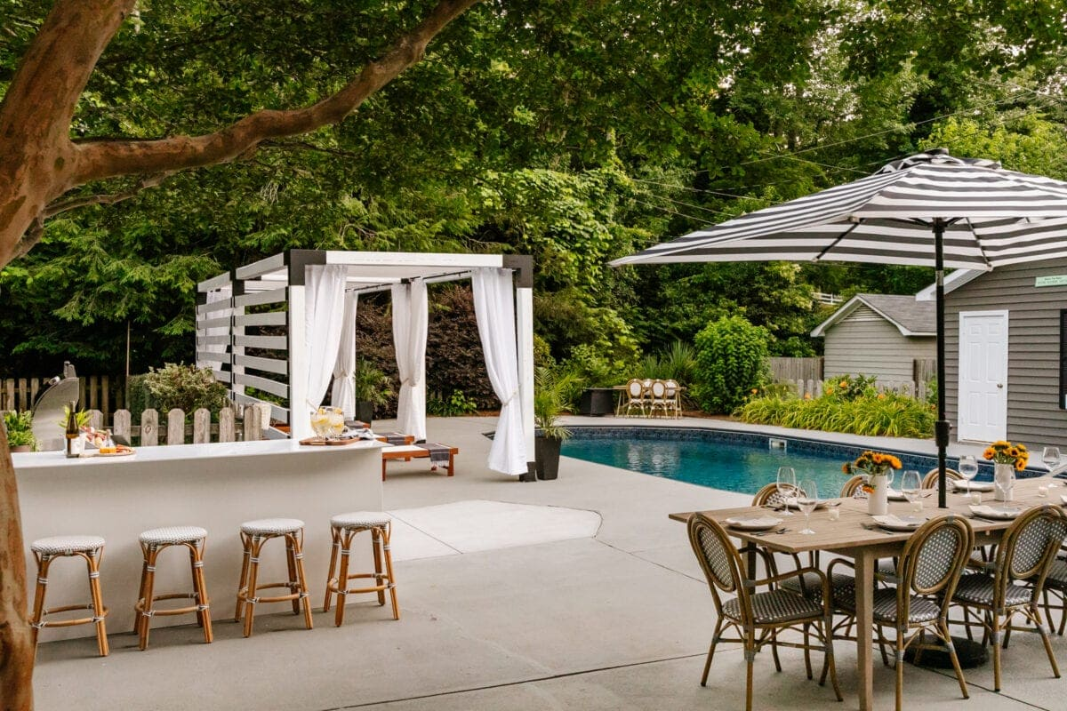 DIY pergola cabana modular outdoor kitchen and outdoor dining table with swimming pool in a backyard