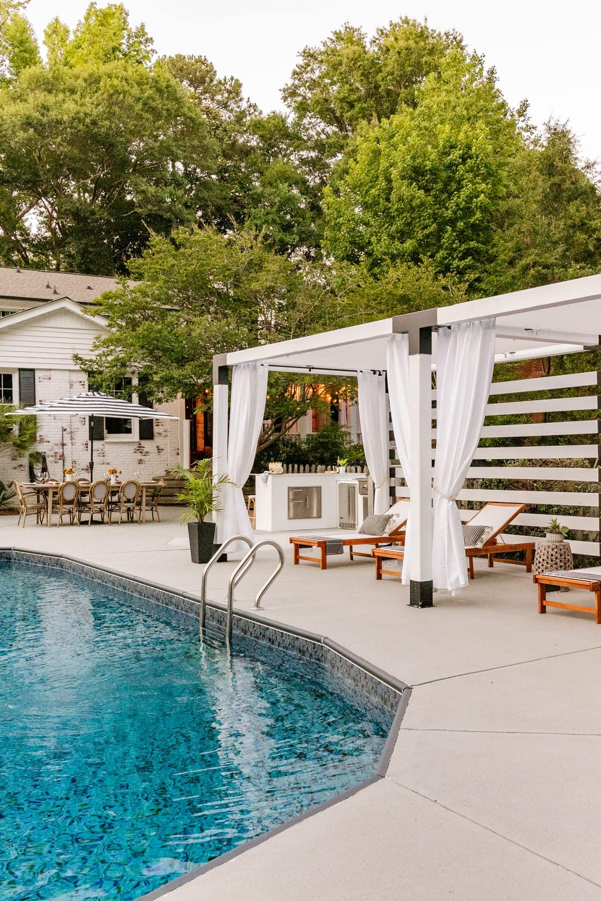 backyard with pool outdoor kitchen pergola cabana and outdoor dining table
