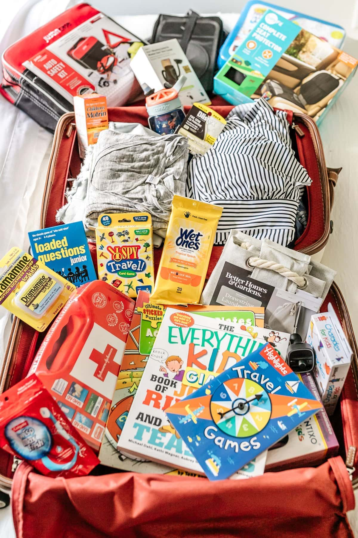 suitcase packed with travel essentials like travel games, first aid kit, wet wipes, Dramamine, and car organizers
