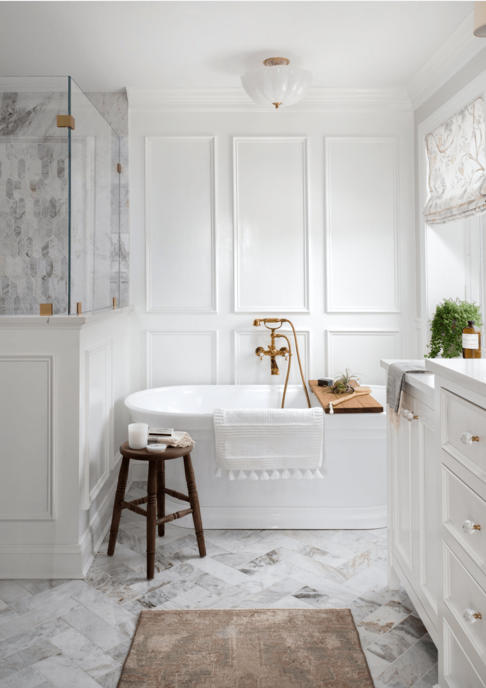 picture frame molding in a bathroom with soaking tub and herringbone tile