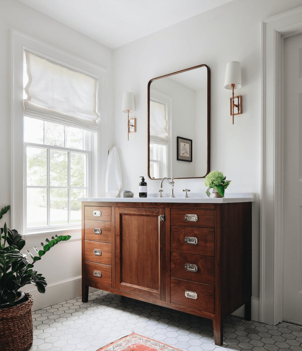 medium toned wood bathroom vanity with hexagon tile and shaded sconces