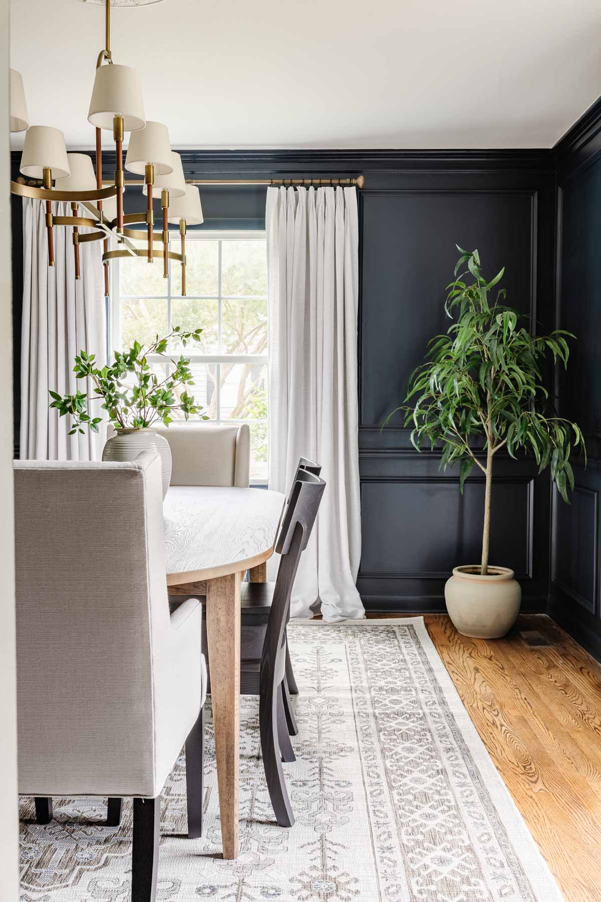 classic modern dining room with mid century modern dining table, navy walls, linen curtains