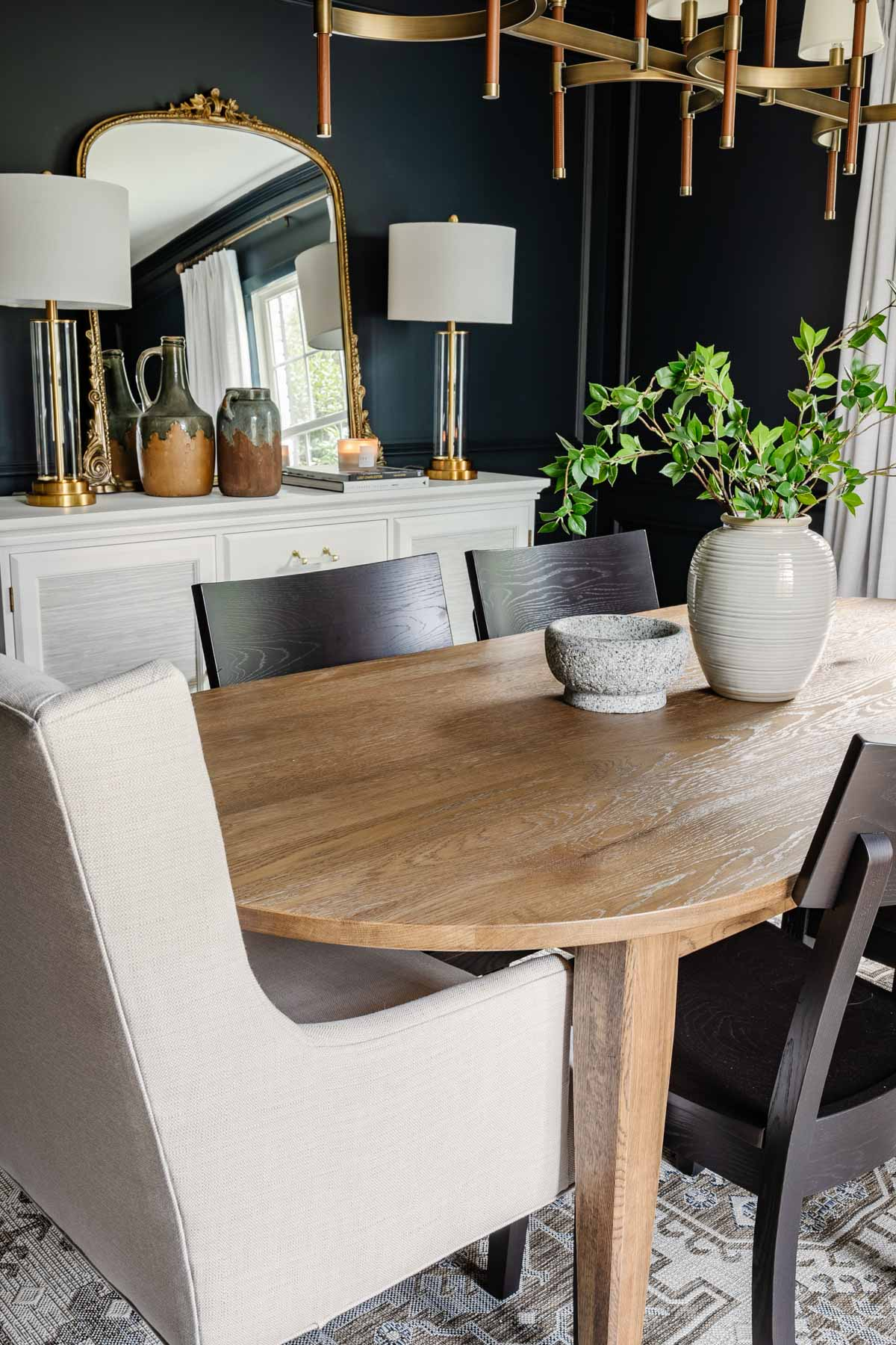 classic modern dining room with navy walls, linen curtains, wood MCM table, black chairs, and French mirror