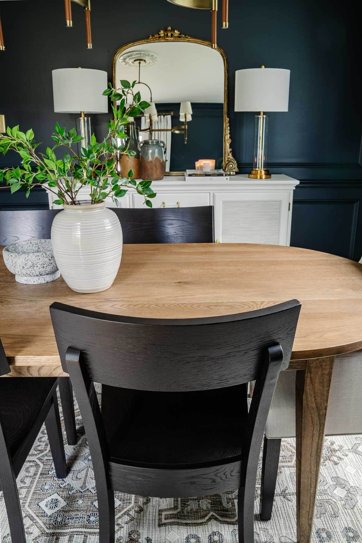 classic modern dining room with midcentury modern table, black chairs, and French mirror