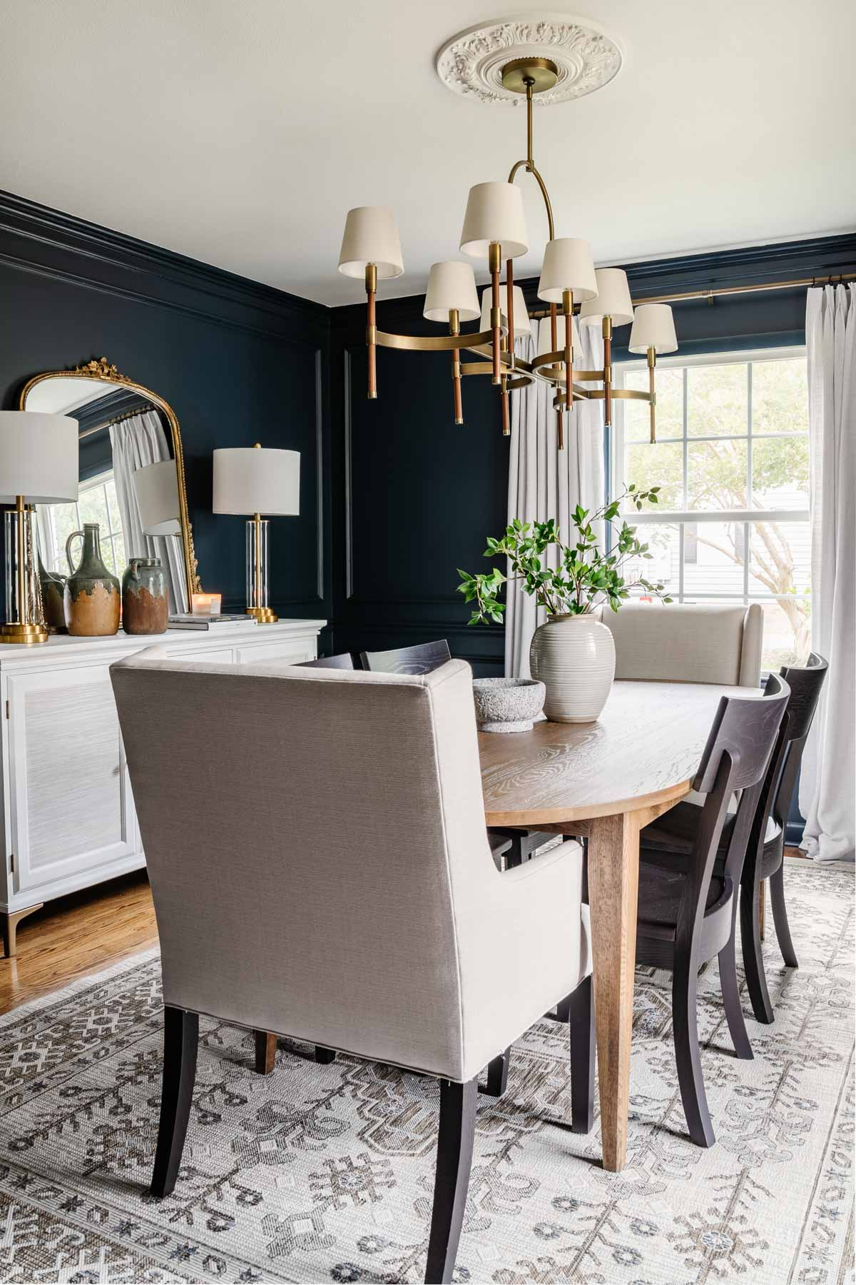 classic modern dining room with mid century modern dining table, navy walls, black chairs, French mirror, and white buffet