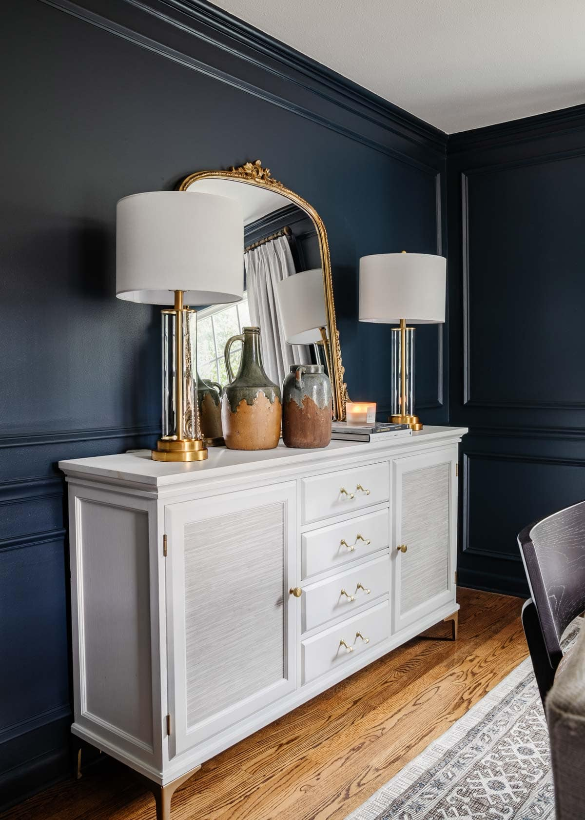 French mirror on white buffet with navy walls