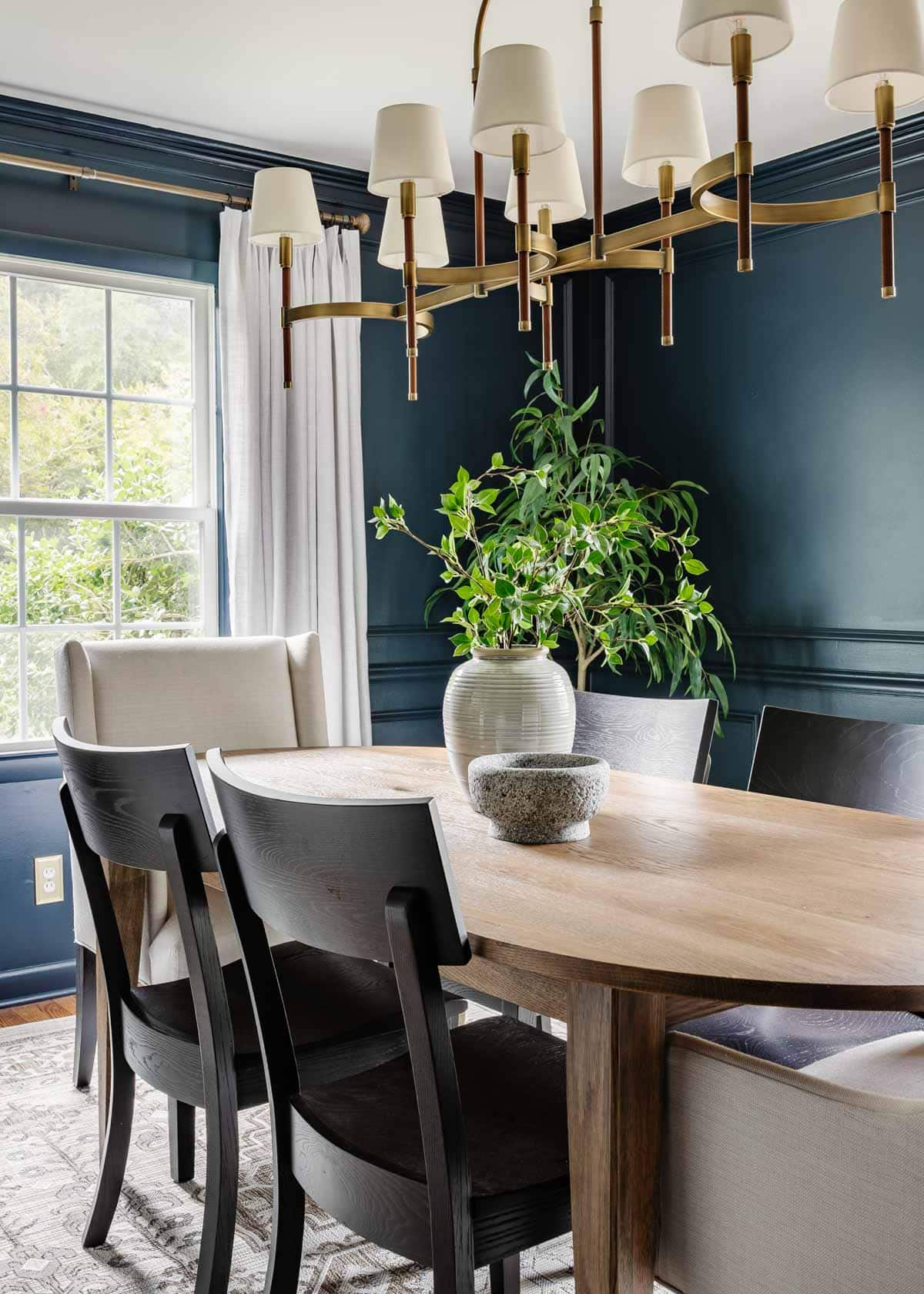 classic modern dining room with navy walls, linen curtains, wood MCM table, and black chairs
