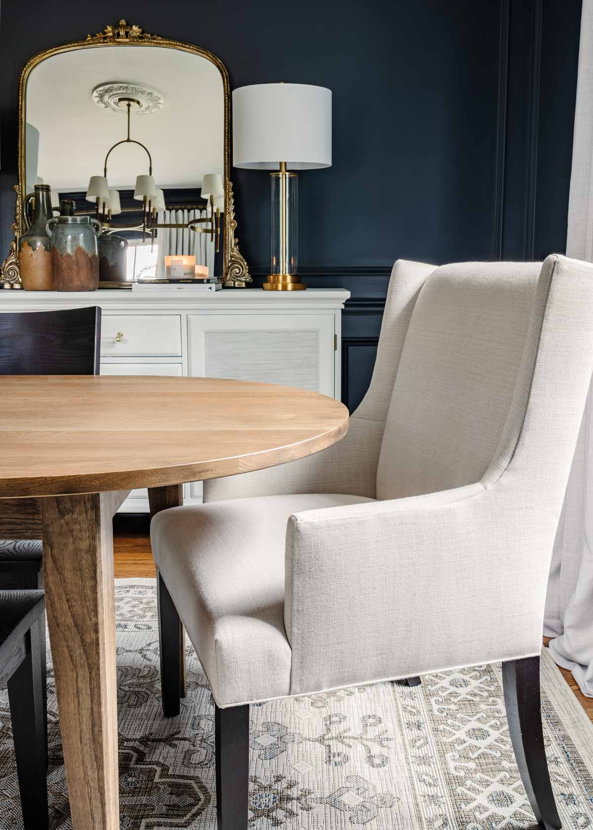 midcentury modern dining table with upholstered chairs, navy walls, and french mirror