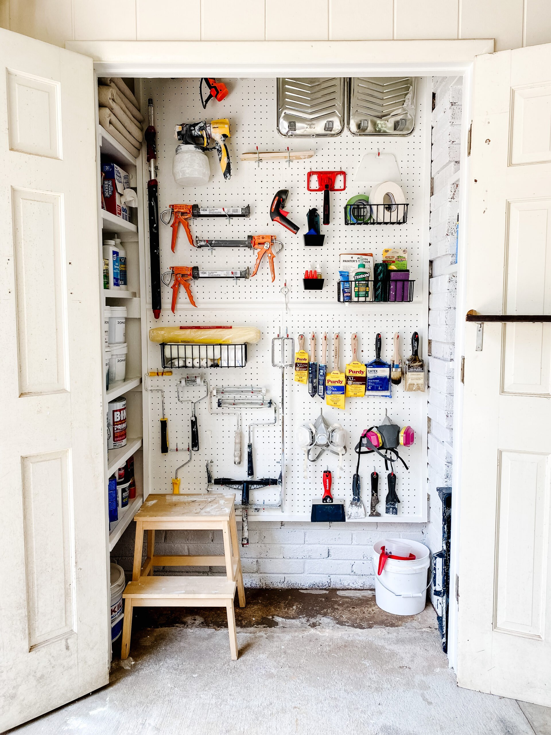 organized paint storage closet with pegboard hooks and DIY shelves