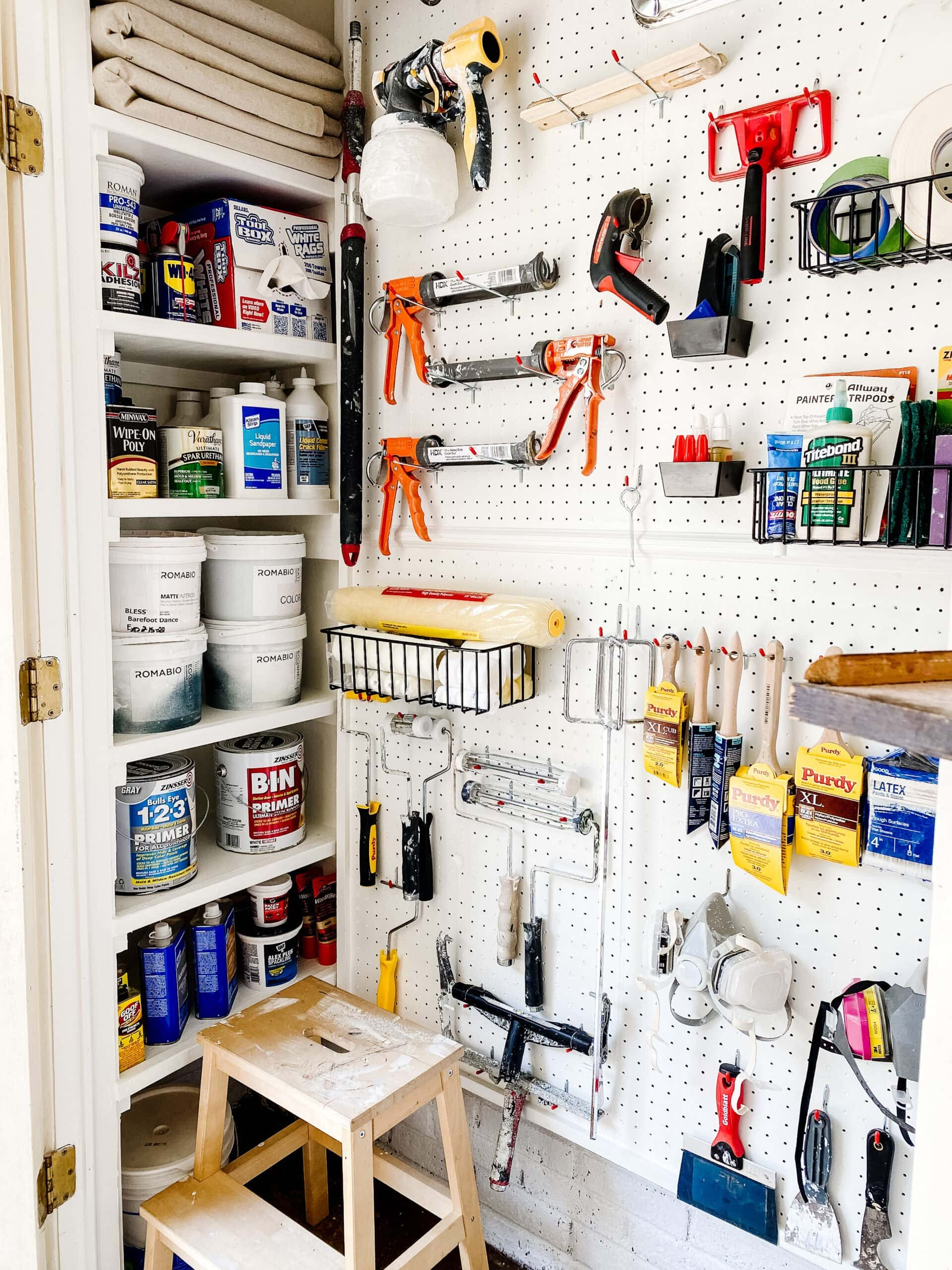 organizing paint supplies with DIY shelves and pegboard hooks and baskets