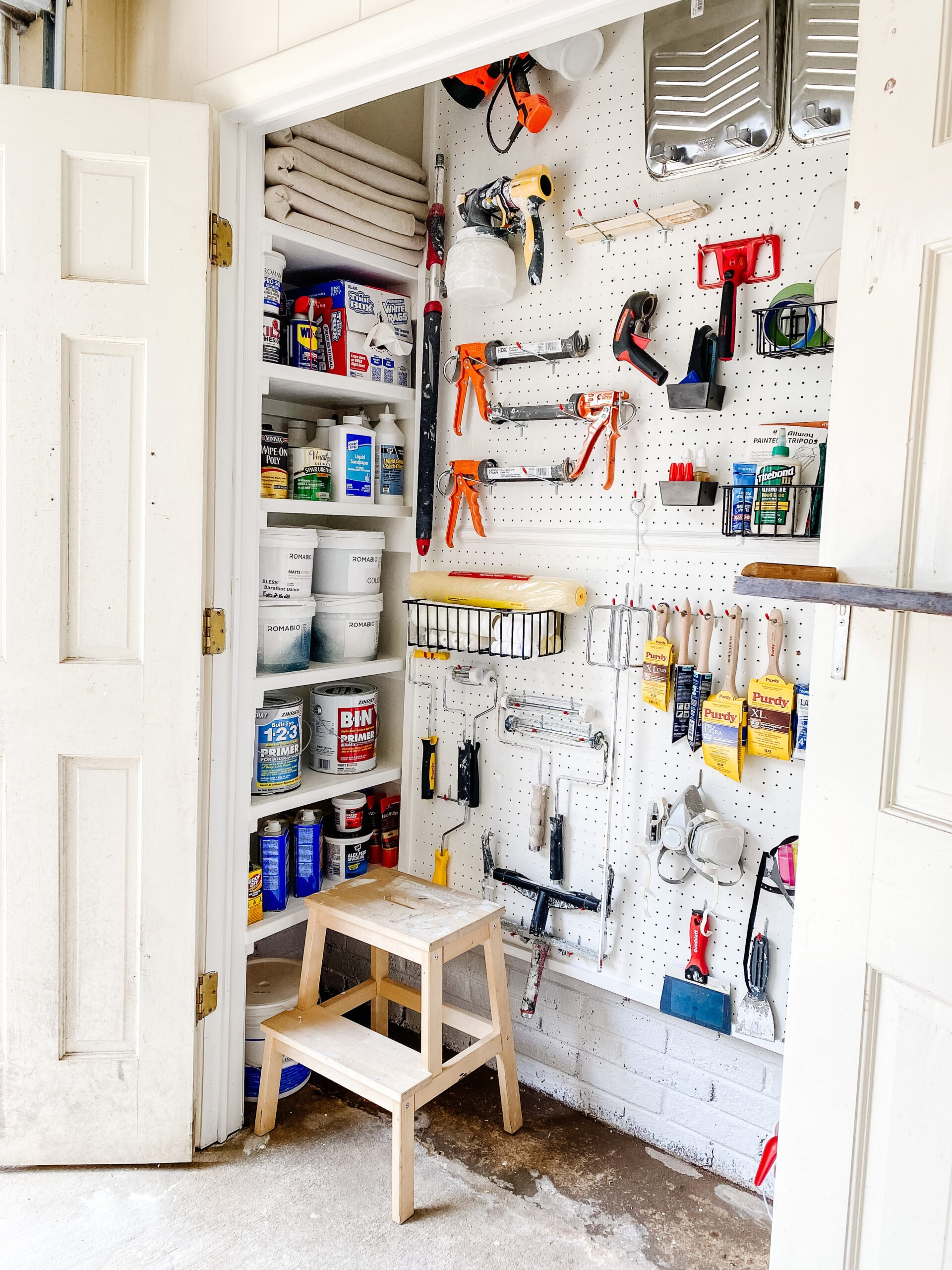 DIY shelves for paint storage and organized paint supplies with pegboard hooks