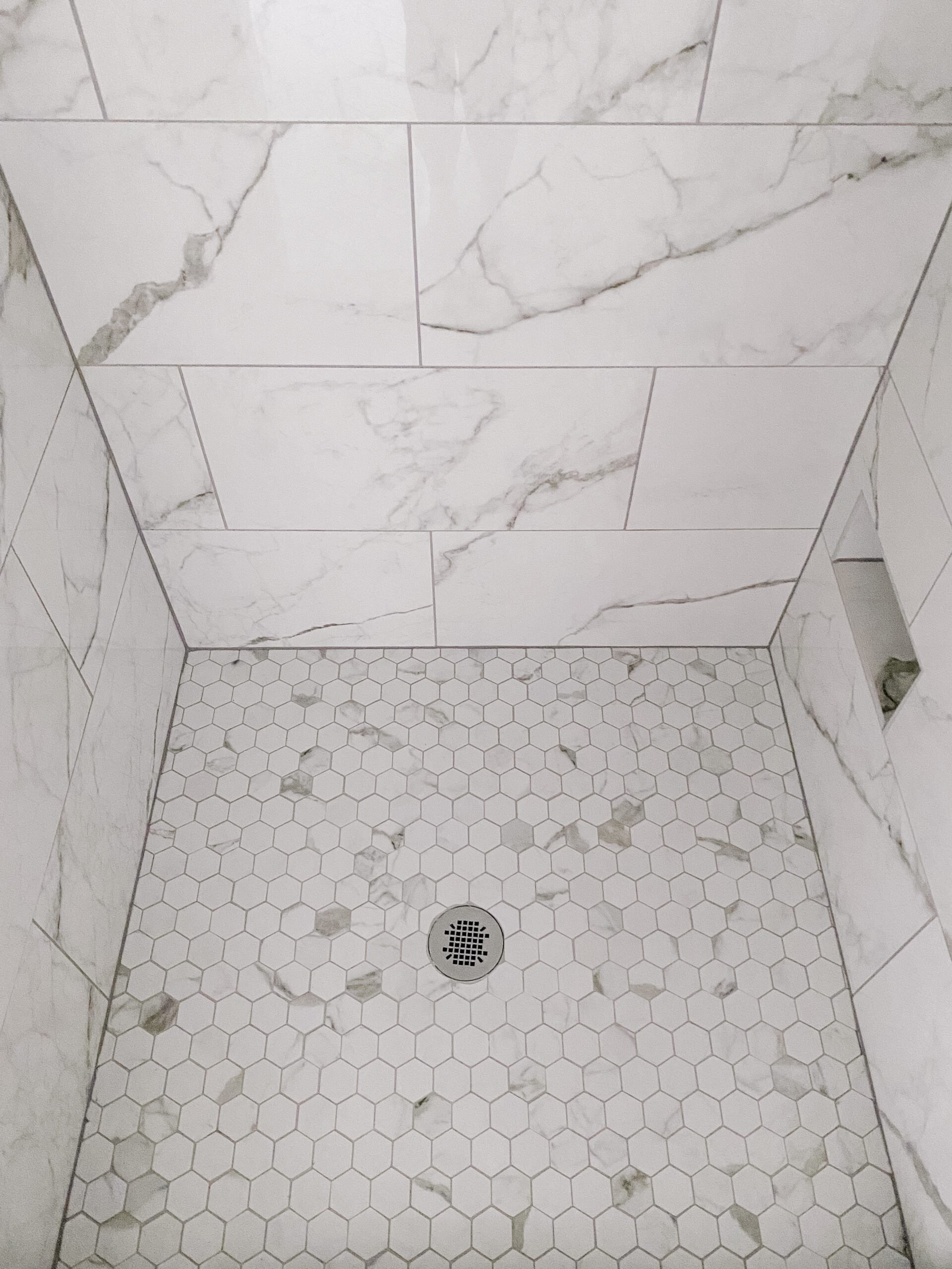 faux marble hexagon tile shower floor with gray grout
